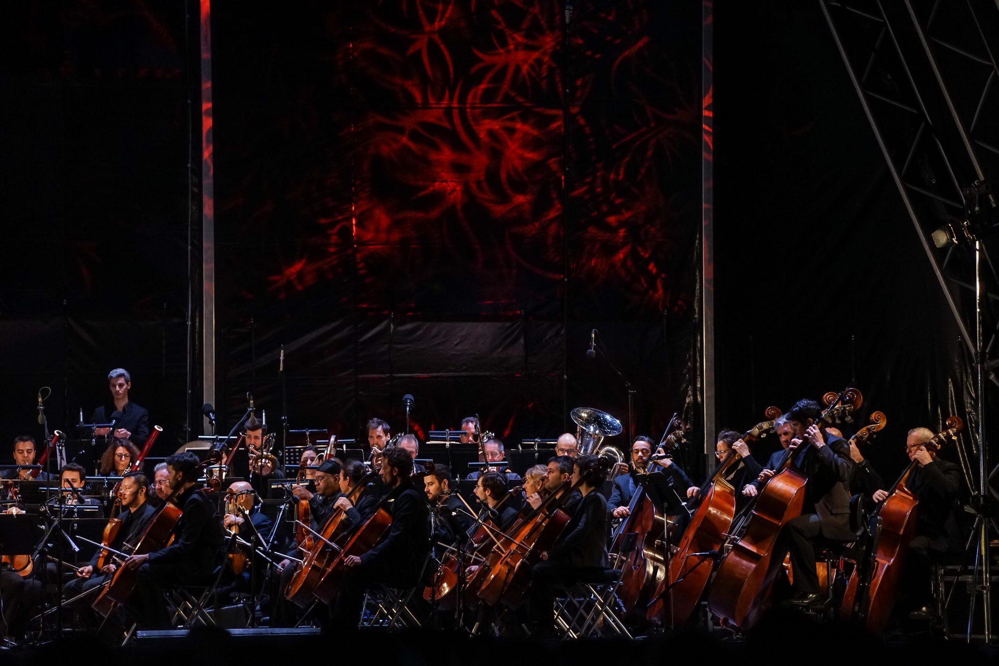 Orquestra no palco e um fundo com efeitos de luz vermelhos
