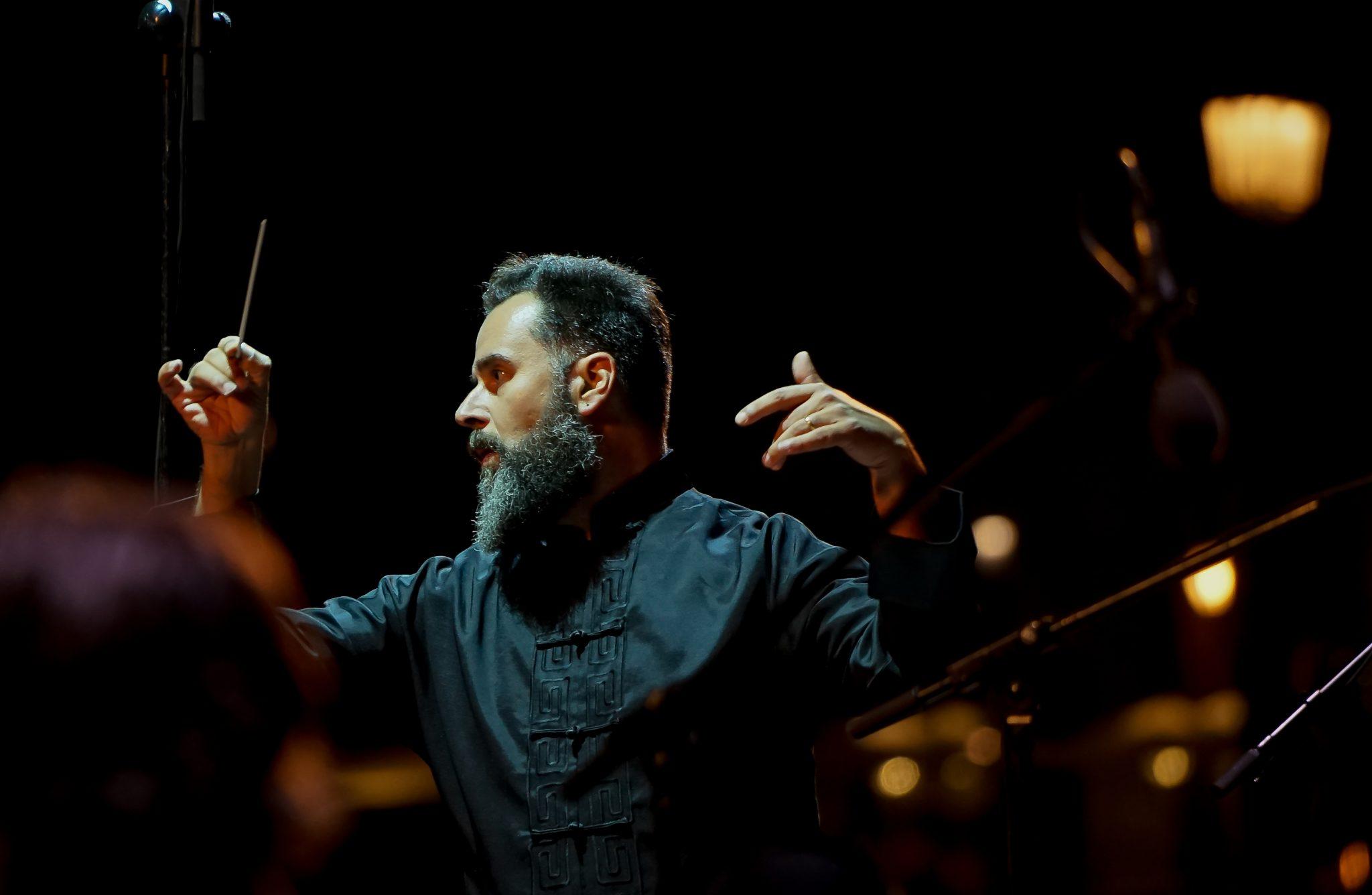 Maestro de barba com as mãos no ar e a batuta na mão que está do lado esquerdo do observador