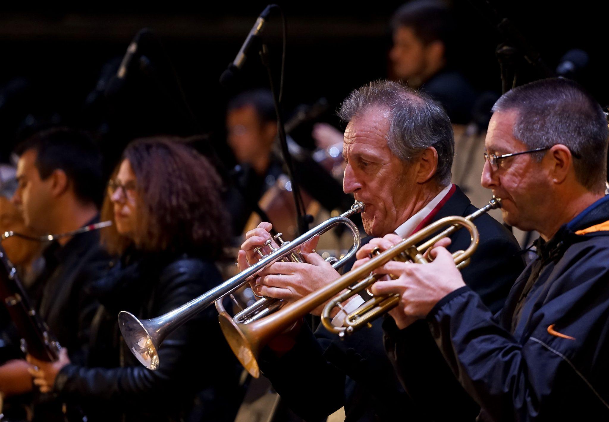 Dois homens tocam trompete em palco, de lado para o observador