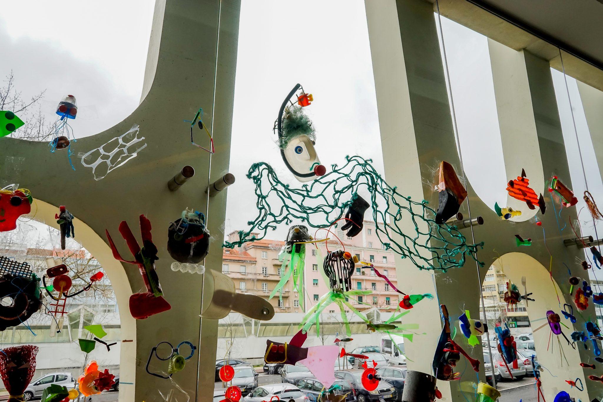 Janela de vidro ampla na qual se encontram colados várias peças criadas com lixo
