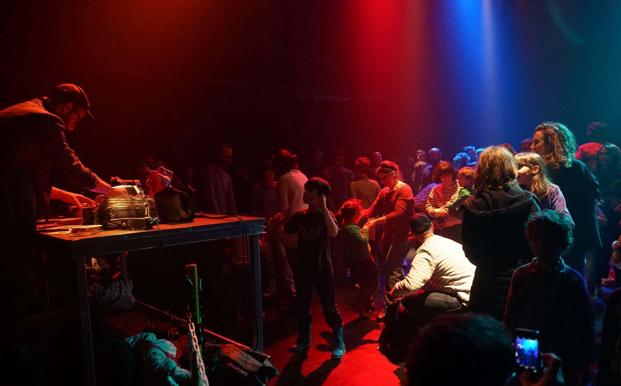 À esquerda do observador, uma mesa de mistura com DJ e, do lado direito, uma pista de dança onde se encontram pessoas de varias idades iluminadas a azul e vermelho