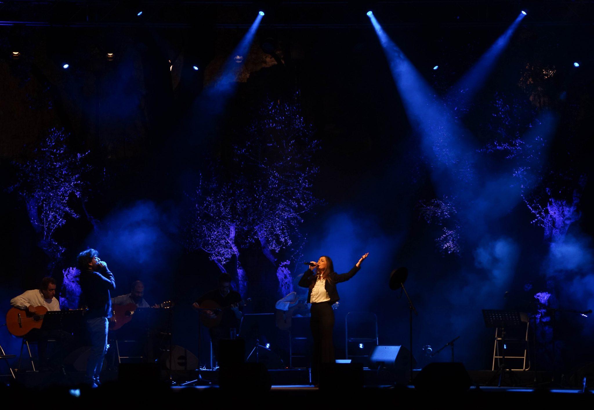 Ana Sofia Varela ao centro da imagem canta acompanhada no palco do Castelo de S. Jorge, iluminado em tons de azul