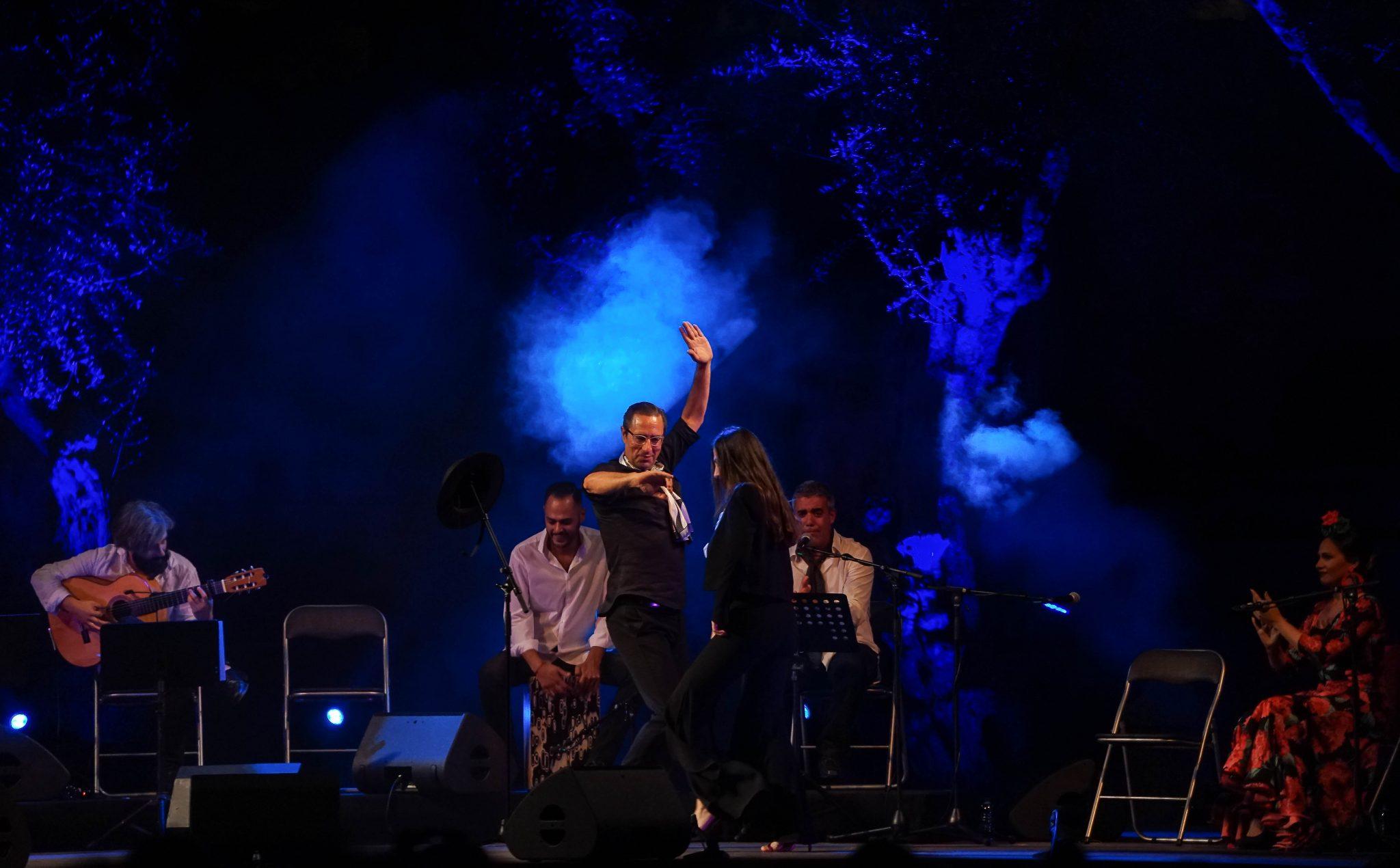 No centro da imagem, um homem e uma mulher dançam flamenco, acompanhados por músicos ao vivo. Do lado direito para o observador, uma mulher com trajes coloridos e floridos acompanha o ritmo com palmas