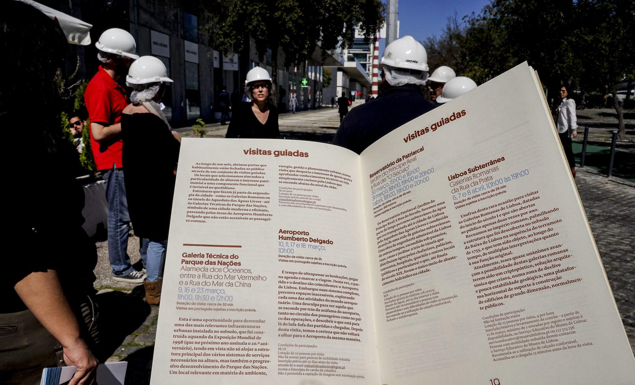 Pormenor de um livro aberto onde se podem ler várias informações. Em segundo plano, desfocadas, estão várias pessoas com capacetes de segurança brancos