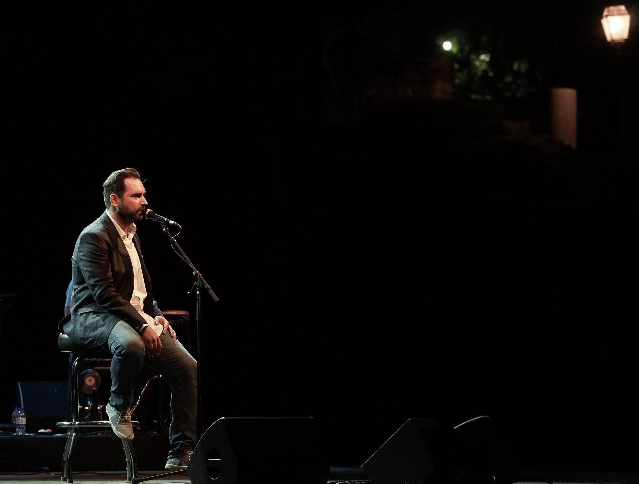 Marco Rodrigues a cantar, sentado num banco