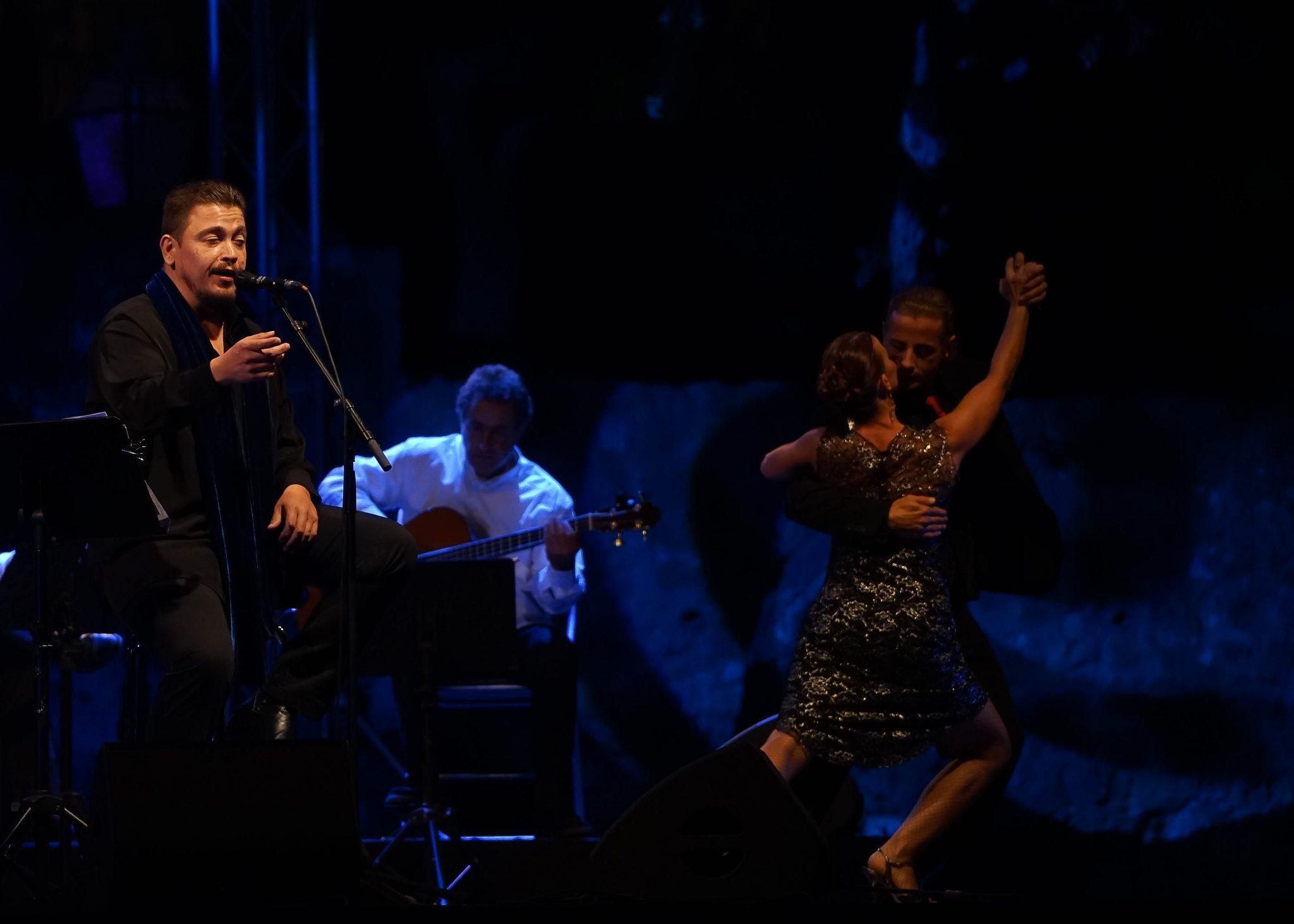 Um homem e uma mulher dançar em palco, acompanhados por música e voz de Ricardo Ribeiro