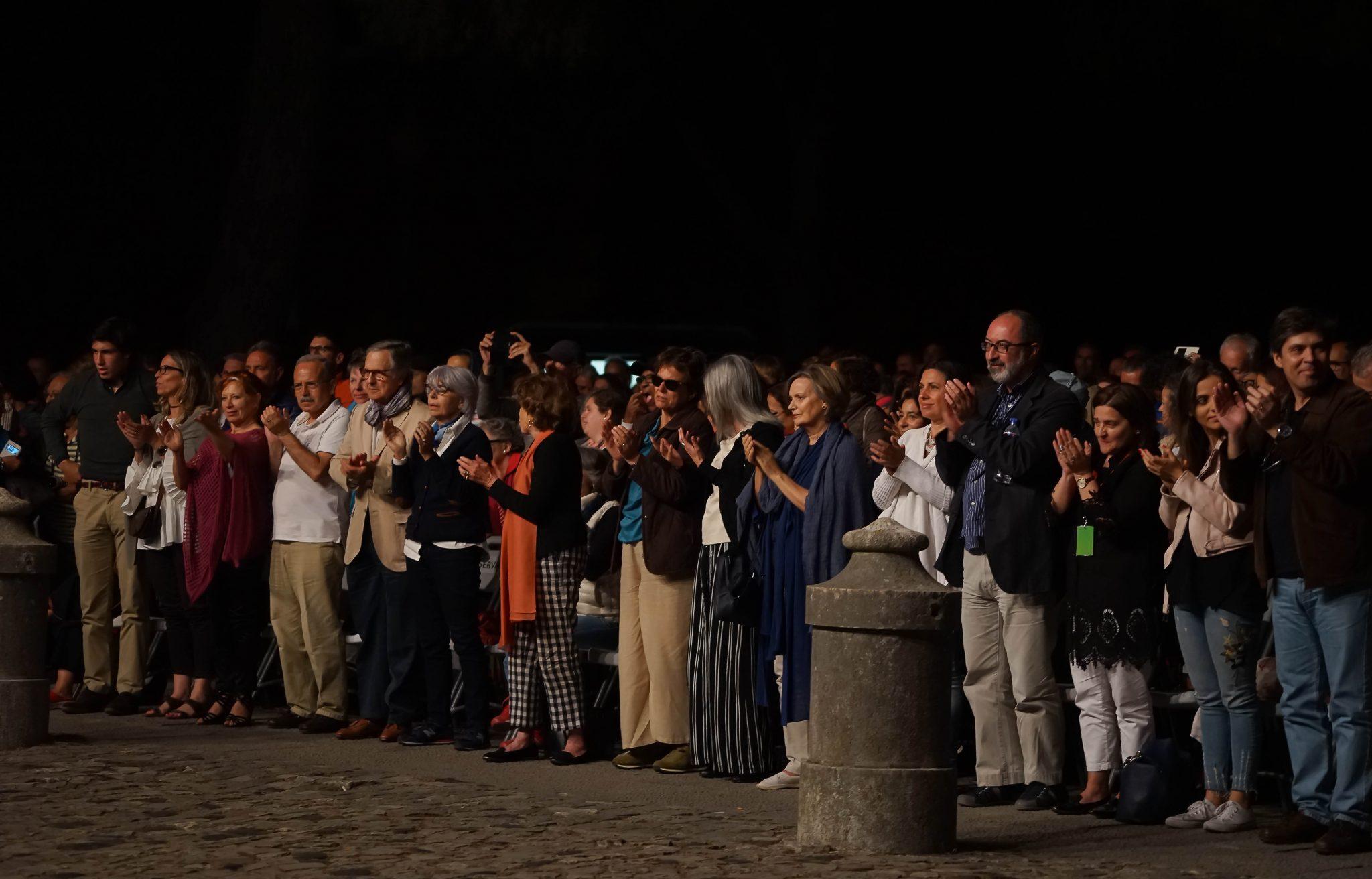 Várias pessoas de pé, a aplaudir