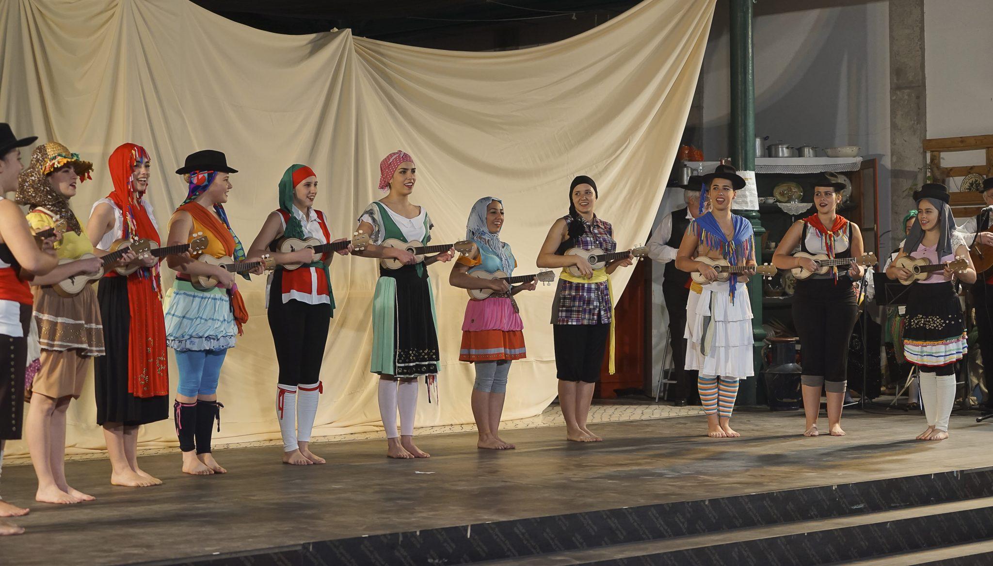 Grupo de mulheres em cima de um palco, de lado para o observador, a tocar cavaquinho, vestidas com trajes típicos de várias regiões de Portugal