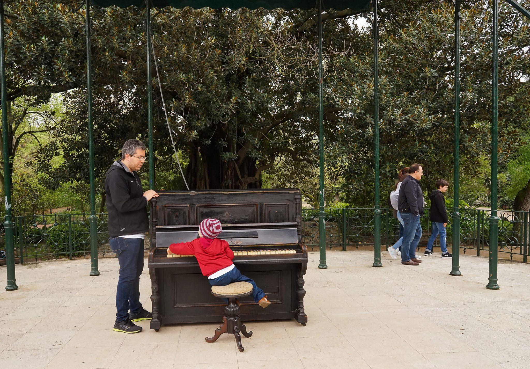 Uma criança toca num piano instalado no meio de um jardim, sob a observação de um adulto debruçado no lado esquerdo do instrumento.
