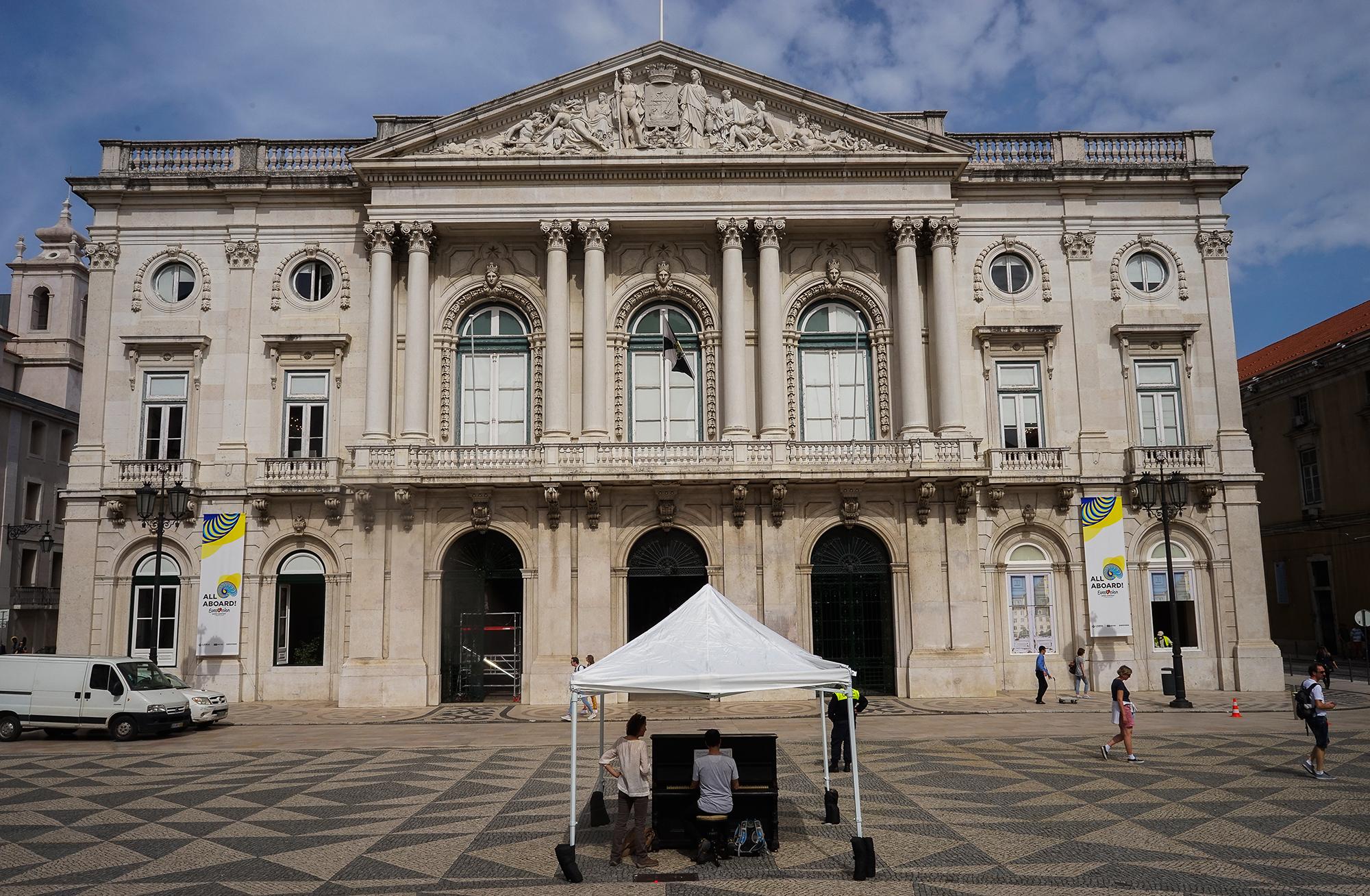 Com a Câmara Municipal de Lisboa, como pano de fundo, de frente para o observador, um piano no meio da Praça do Município quase vazia é tocado por uma pessoa.