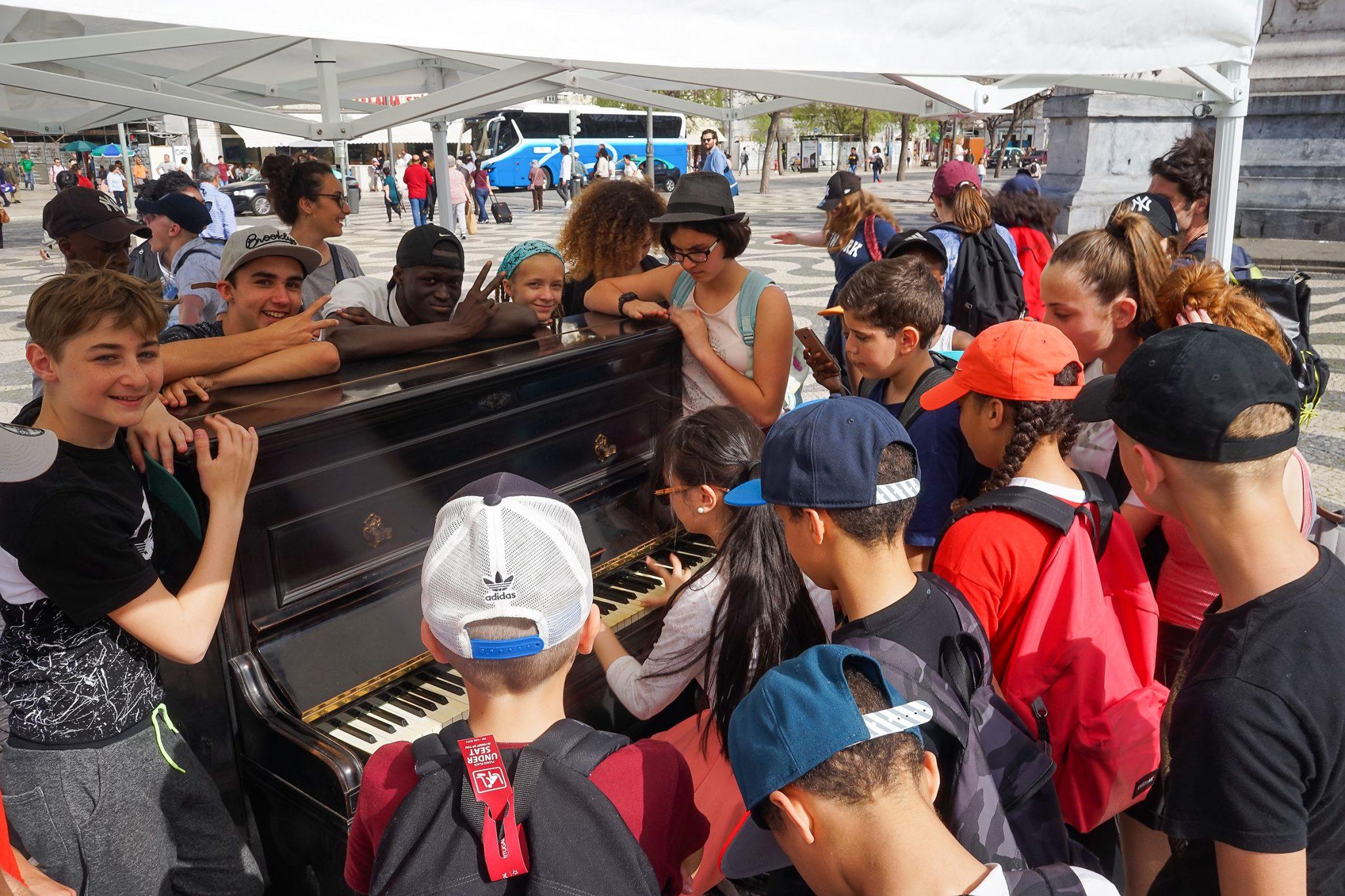 Um grupo de crianças a rodear um piano no meio da rua, enquanto alguém toca.