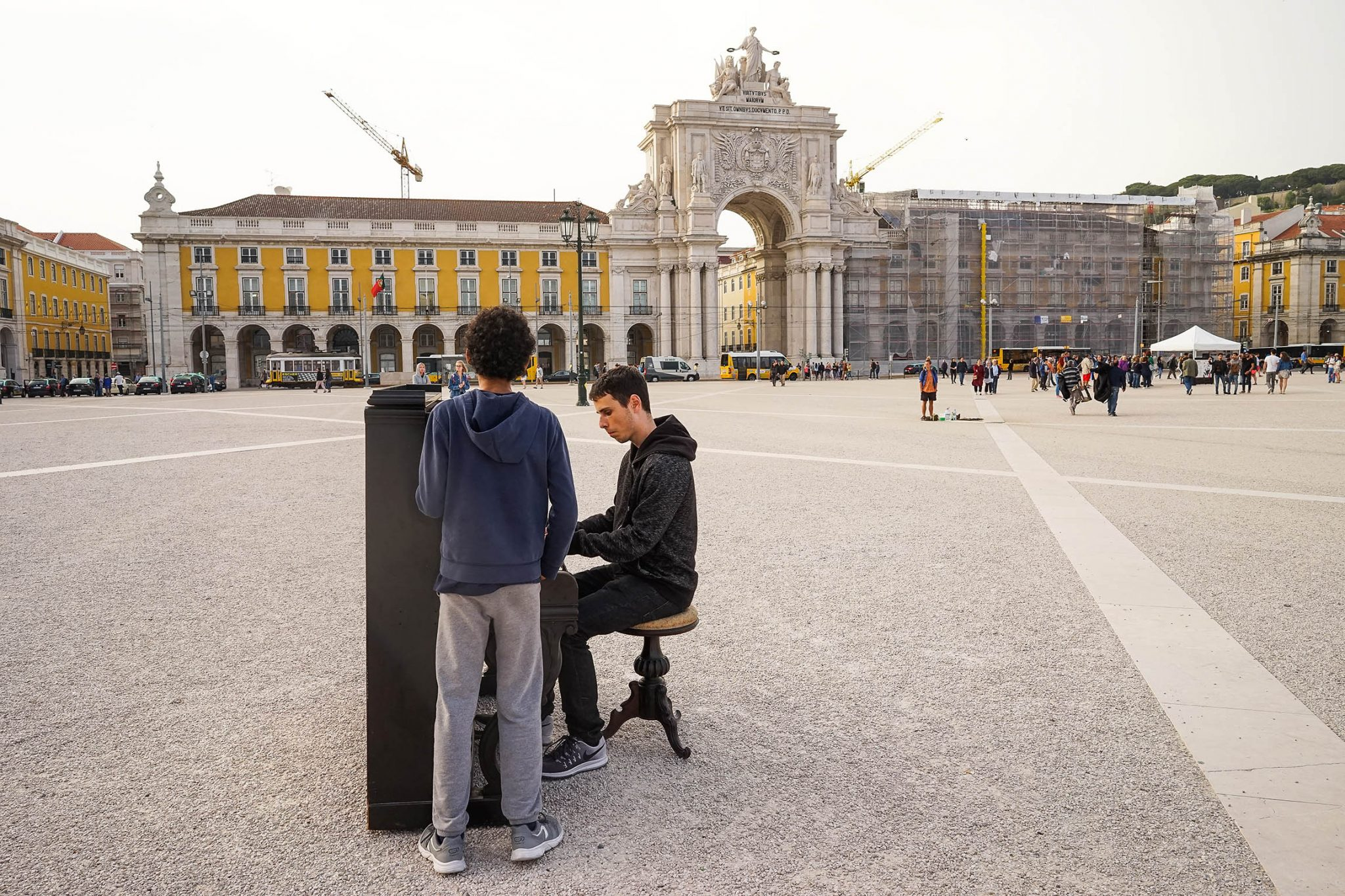 A Praça do Comércio, com o Arco da Rua Augusta em destaque, serve de cenário a um piano que está a ser tocado por um rapaz, de lado para o observador, para um admirador.