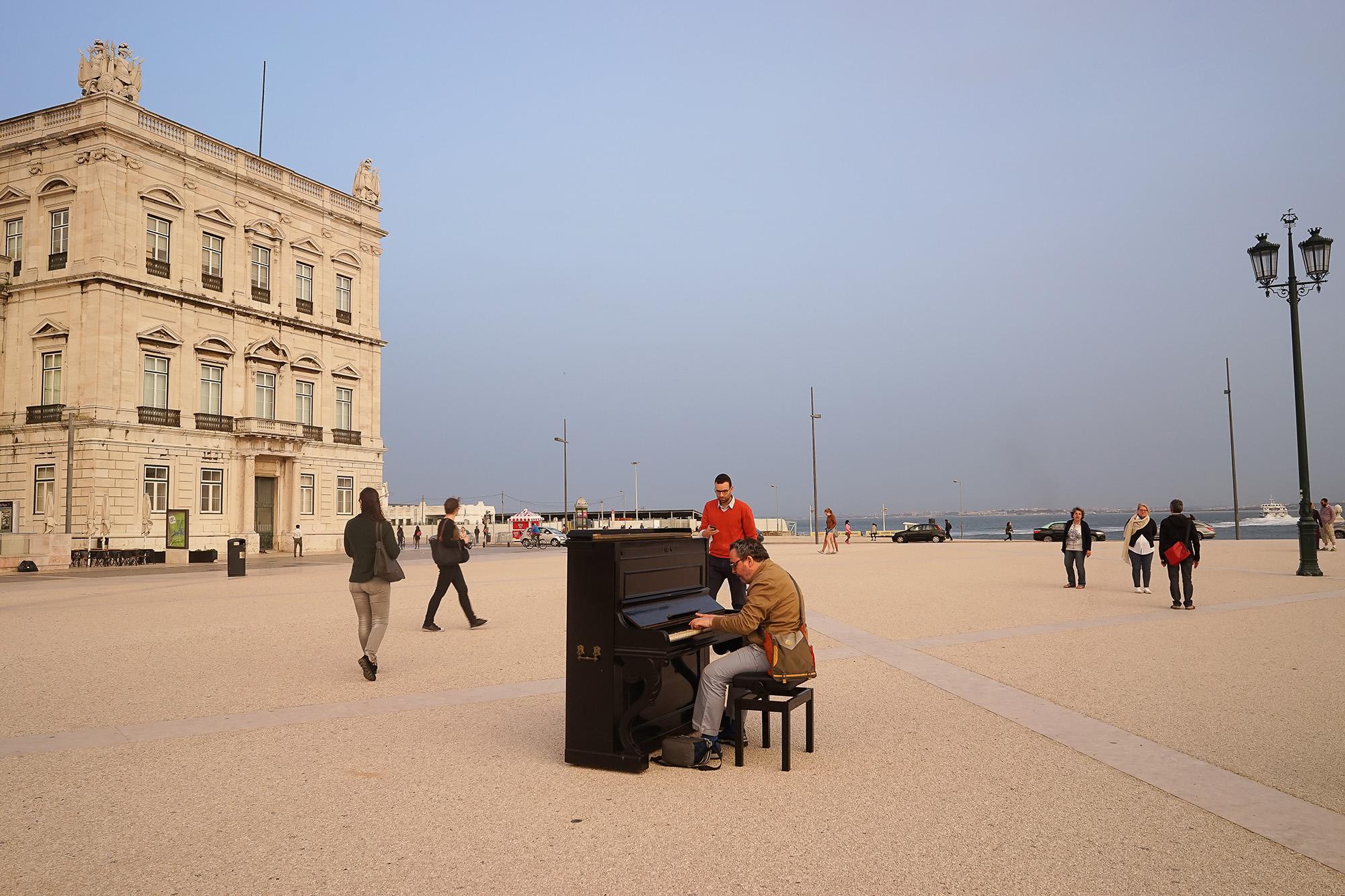 Um piano com um homem a tocar, na Praça do Comércio, de lado para o observador, entre o Torreão, do lado esquerdo, e um candeeiro, à direita.