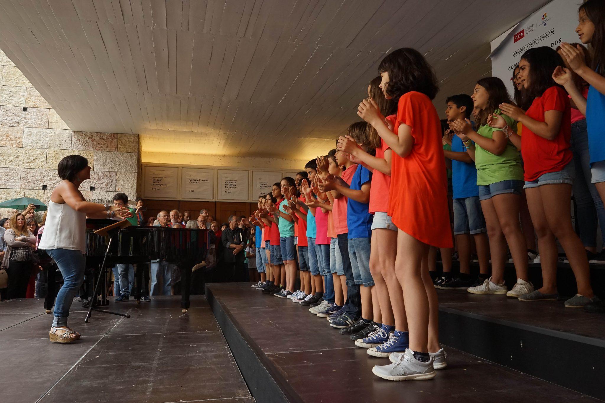 Crianças com t-shirts de várias cores, de lado para o observador, atuam sob as ordens da Maestrina (à esquerda do observador)