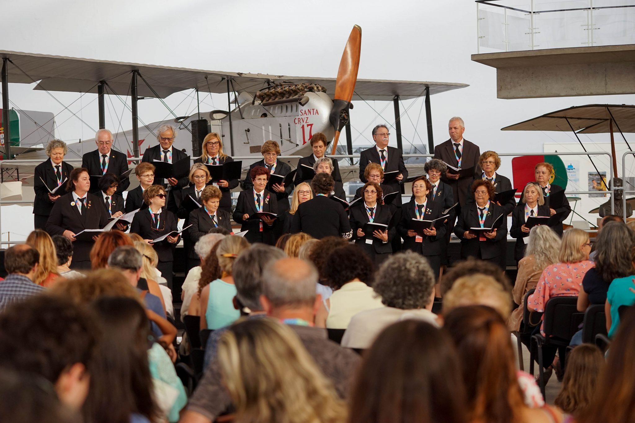 Grupo coral composto por homens e mulheres, vestidos de preto, atua numa sala branca. Atrás, um modelo antigo de avião