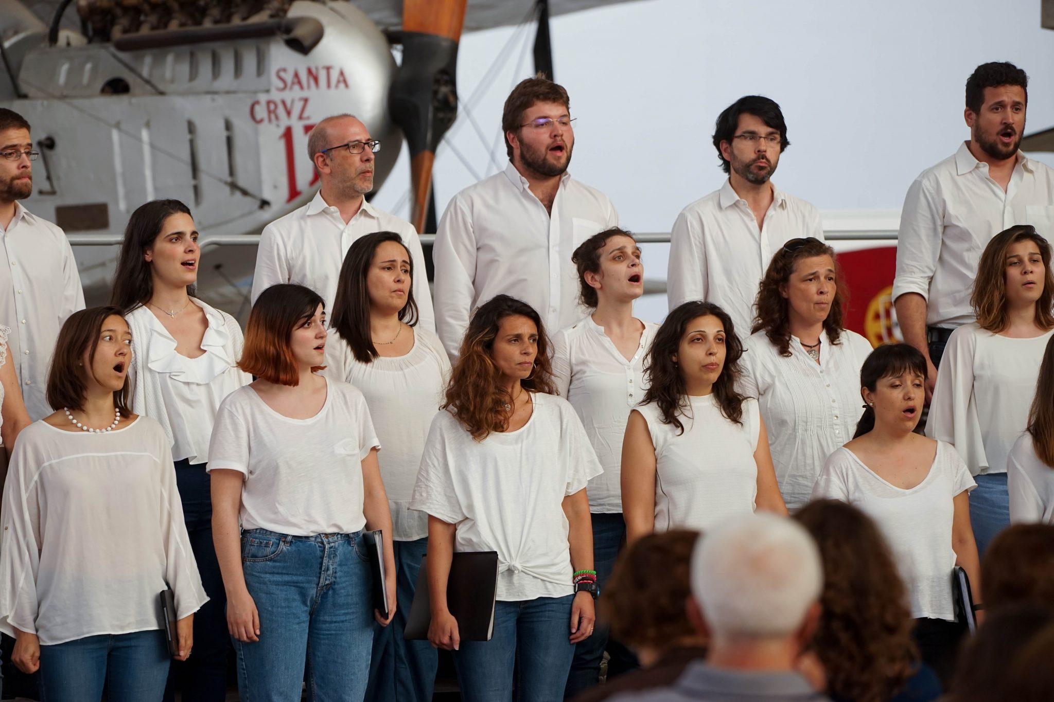 Grupo coral vestido de camisas brancas a cantar