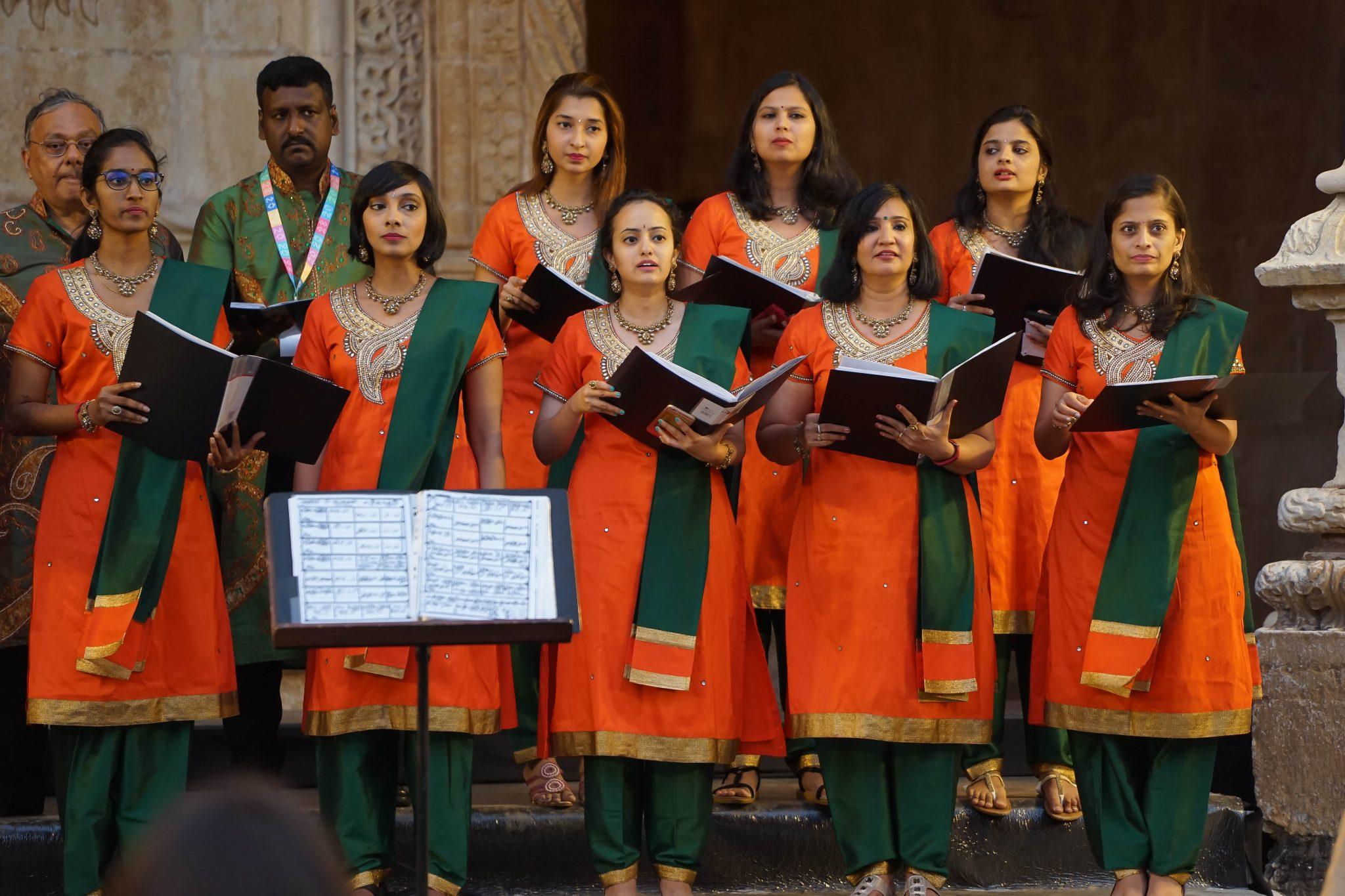 Grupo coral vestido de verde e laranja atuam de frente para o observador com os cadernos das pautas nas mãos