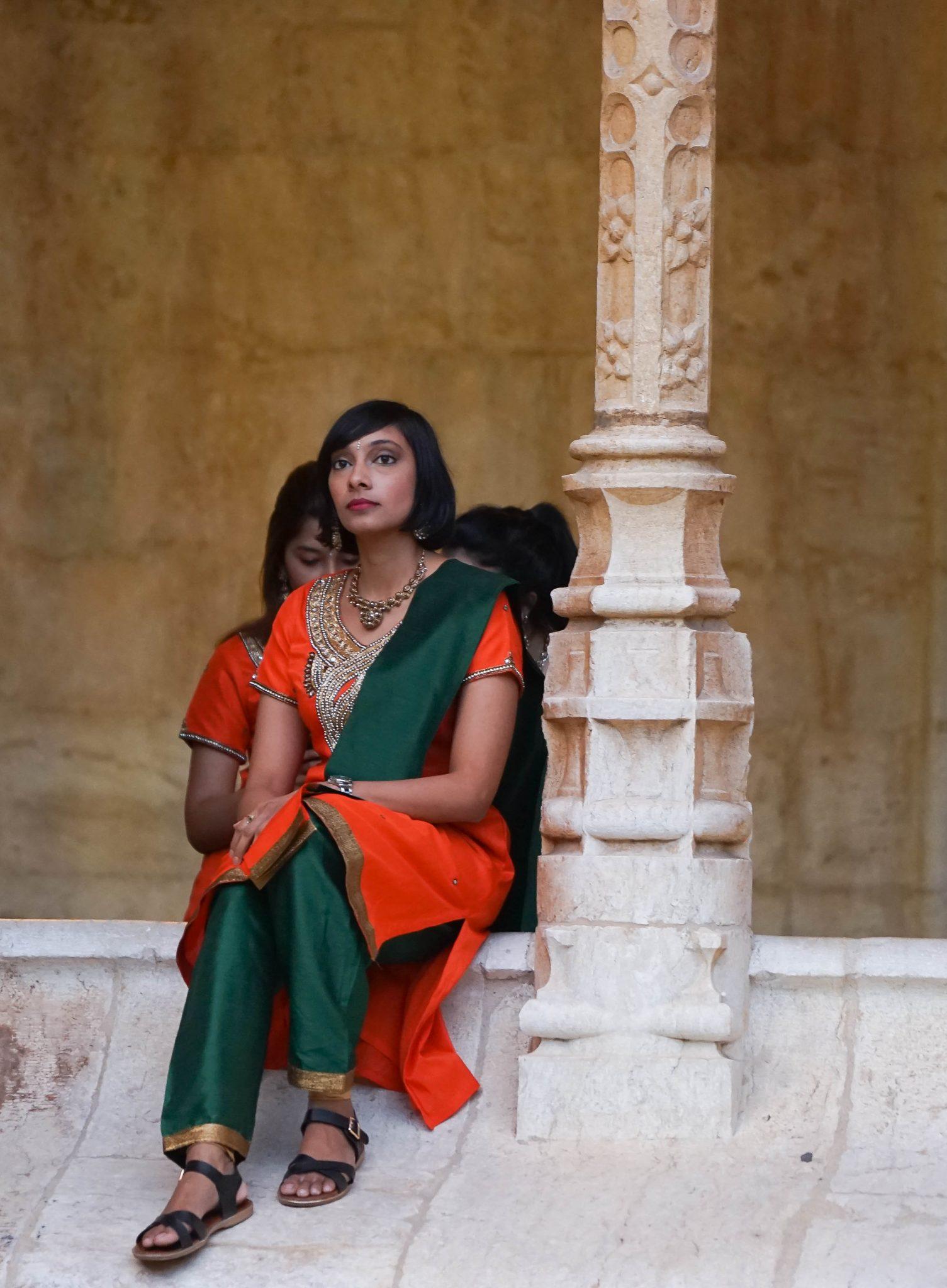 Mulher vestida de laranja e verde sentada no Claustro do Mosteiro dos Jerónimos de frente para o observador