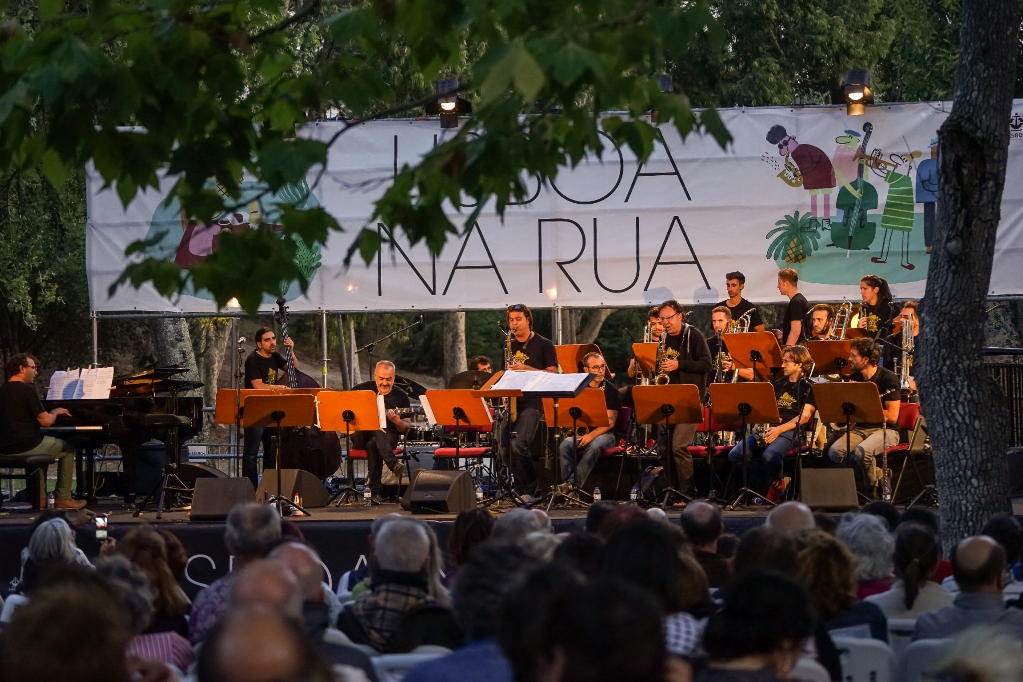 Orquestra de jazz toca num palco enquadrado por árvores. Numa faixa branca com ilustrações pode ler-se LISBOA NA RUA