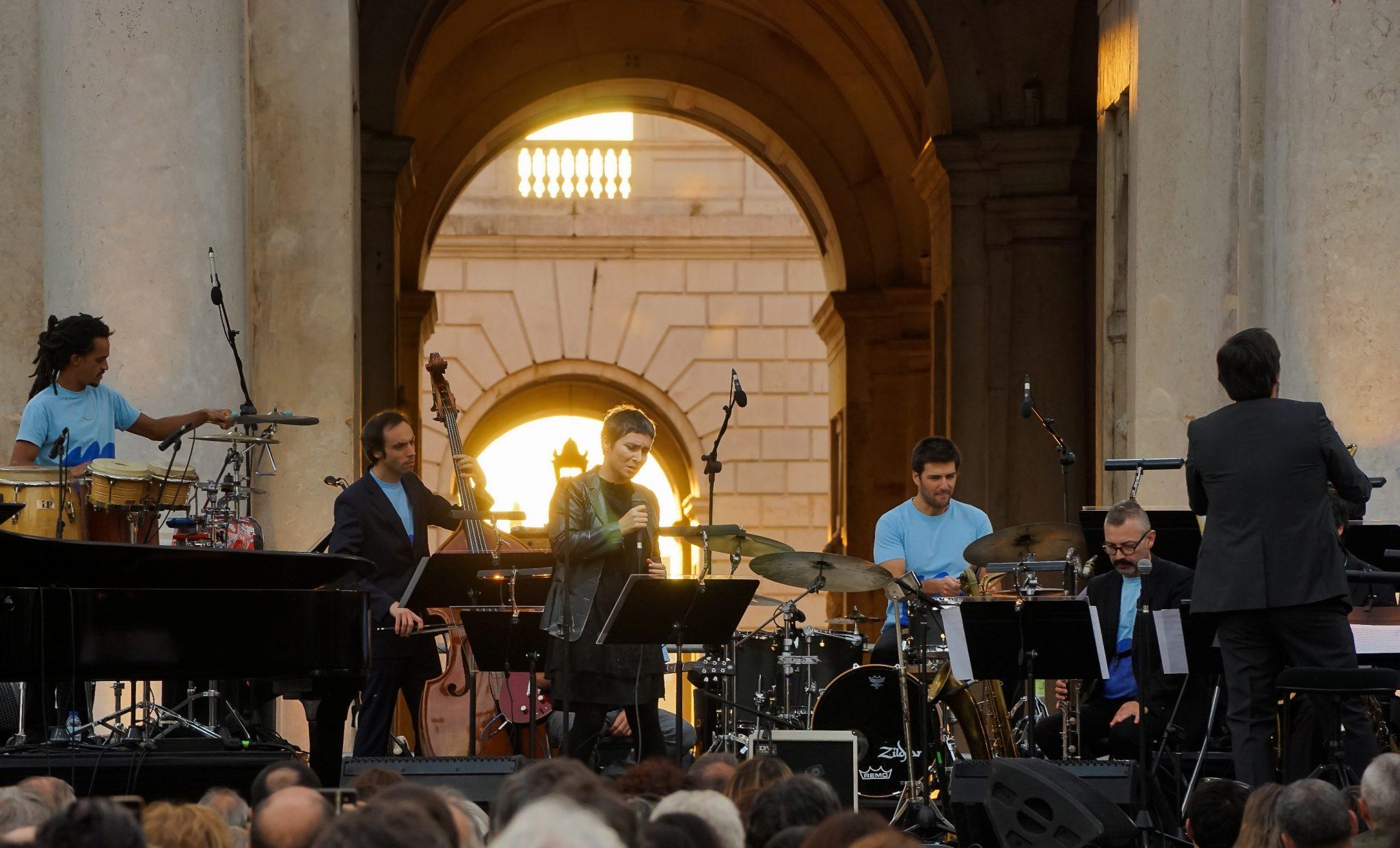 A cantora Manuela Azevedo em cima do palco, rodeada por músicos. Atrás, um pormenor do Palácio da Ajuda com a luz do por do sol a colorir a pedra de tons dourados