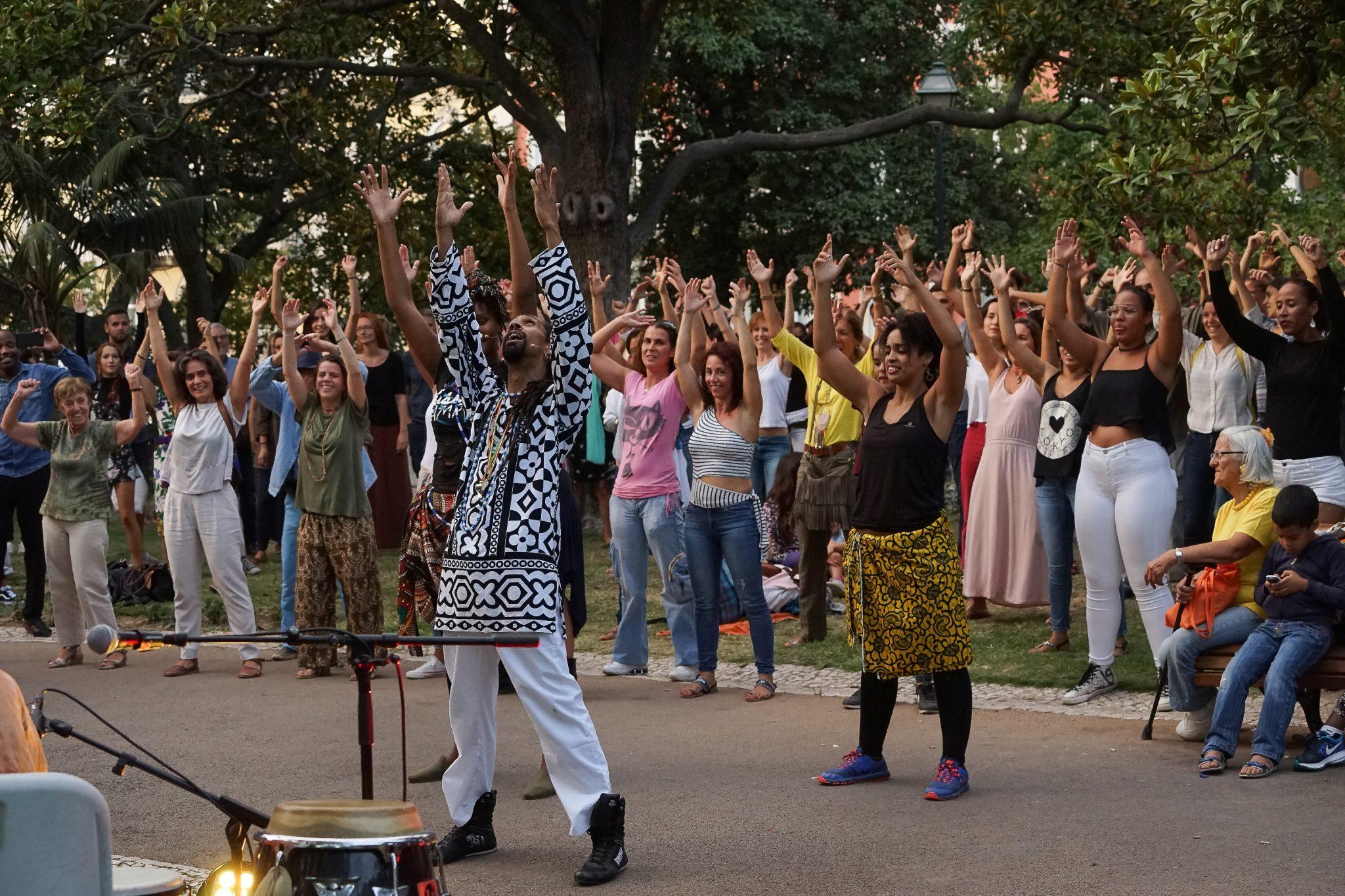 Aula de danças africanas numa zona verde, com várias pessoas de braços no ar e a sorrir