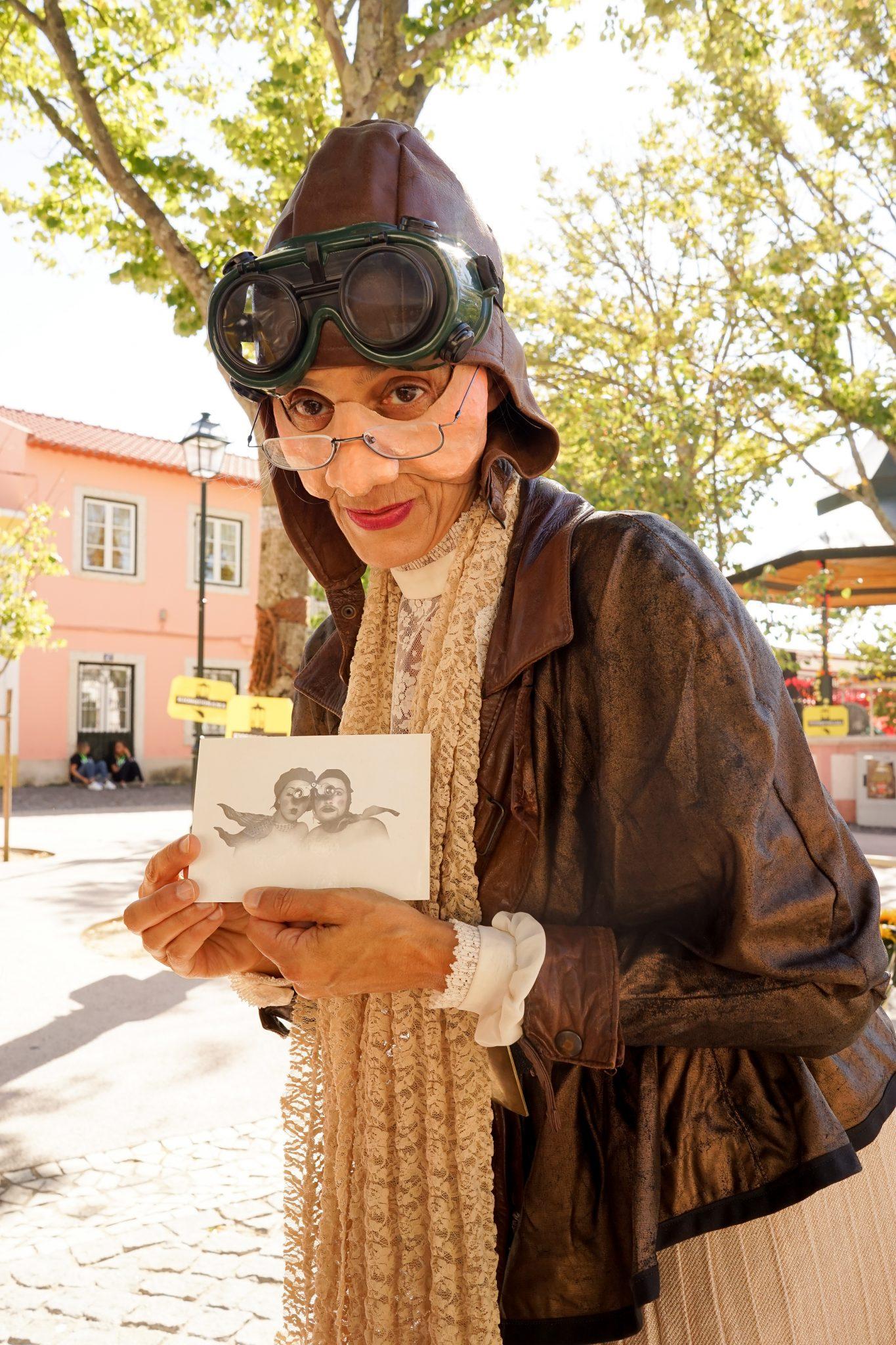 Mulher mascarada de aviadora idosa mostra uma fotografia a preto e branco de frente para o observador
