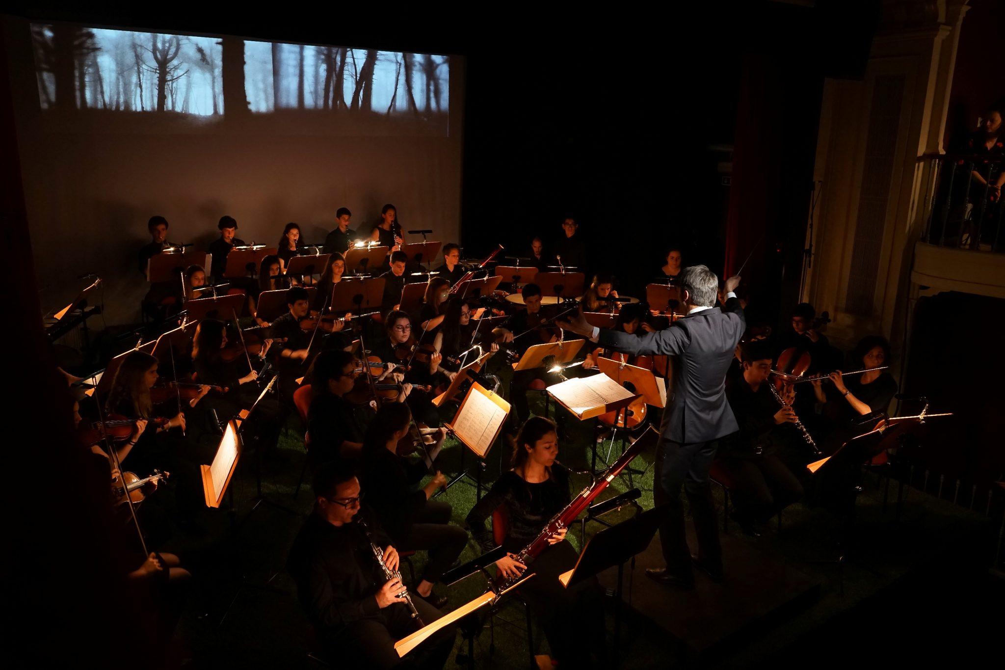 Uma orquestra toca em cima de um palco na diagonal do observador