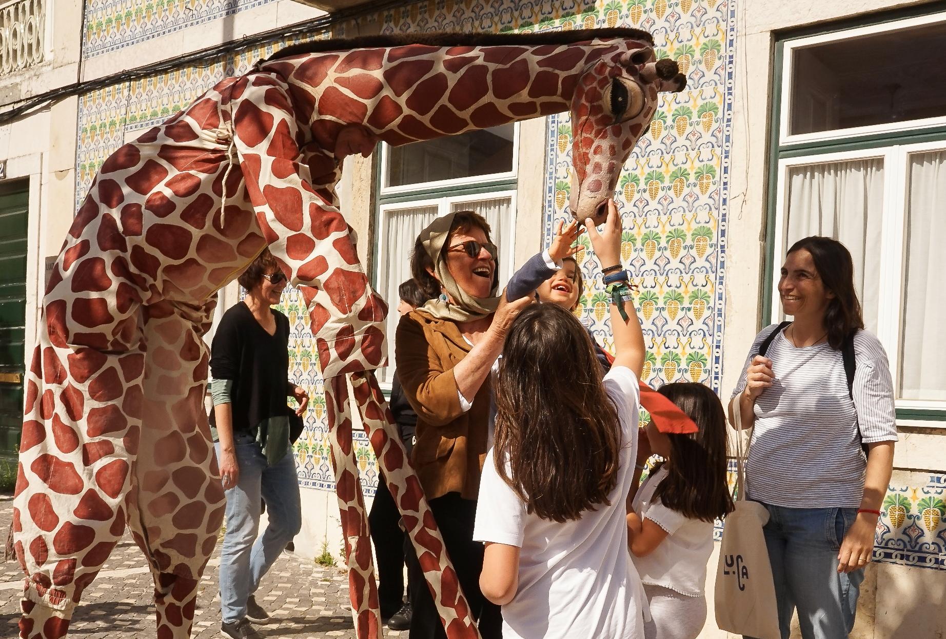 Actor vestido de girafa interage com crianças e adultos