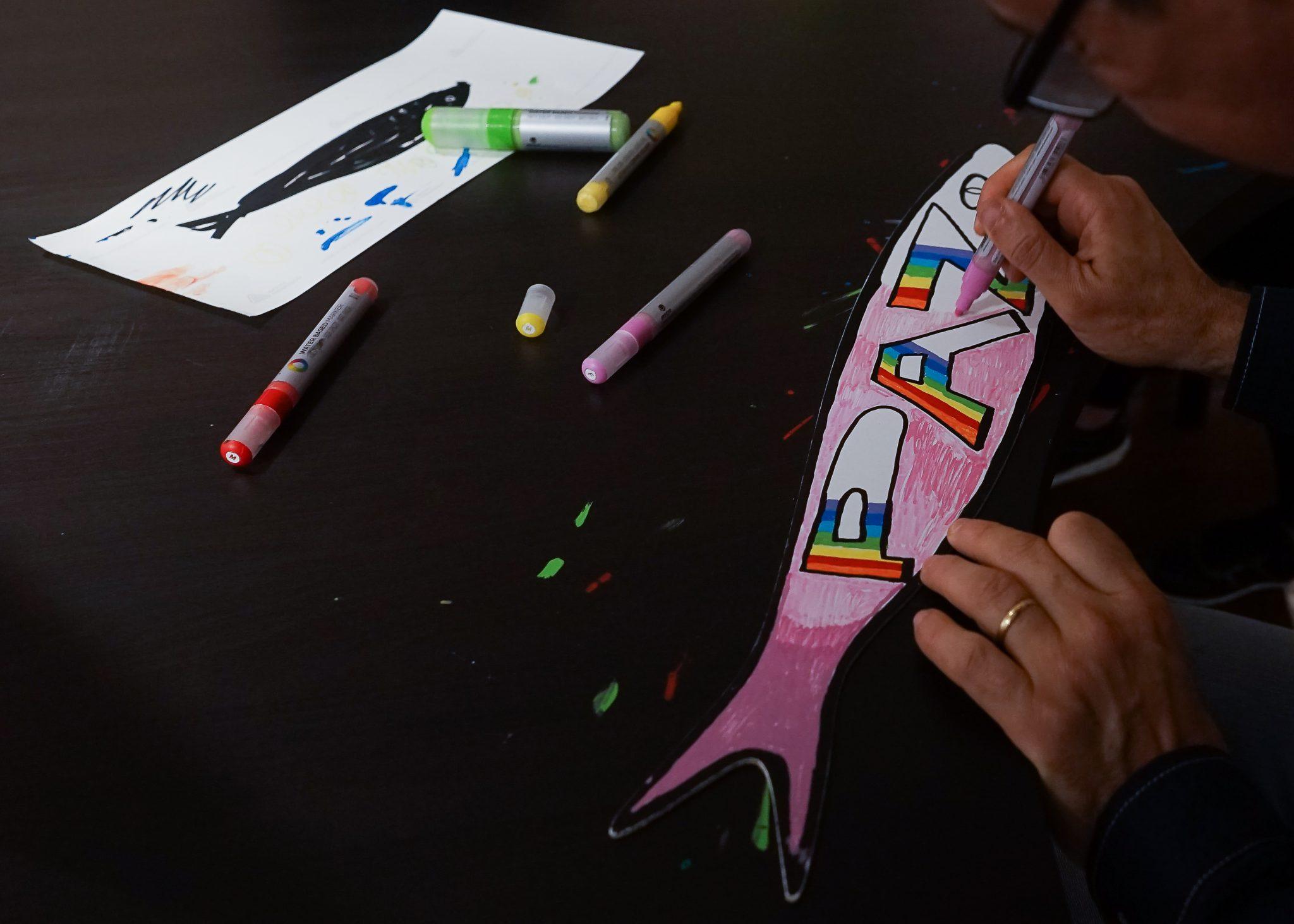Uma pessoa desenha e pinta de cor-de-rosa a palavra PAZ num cartão com a silhueta de uma sardinha em cima de uma mesa preta