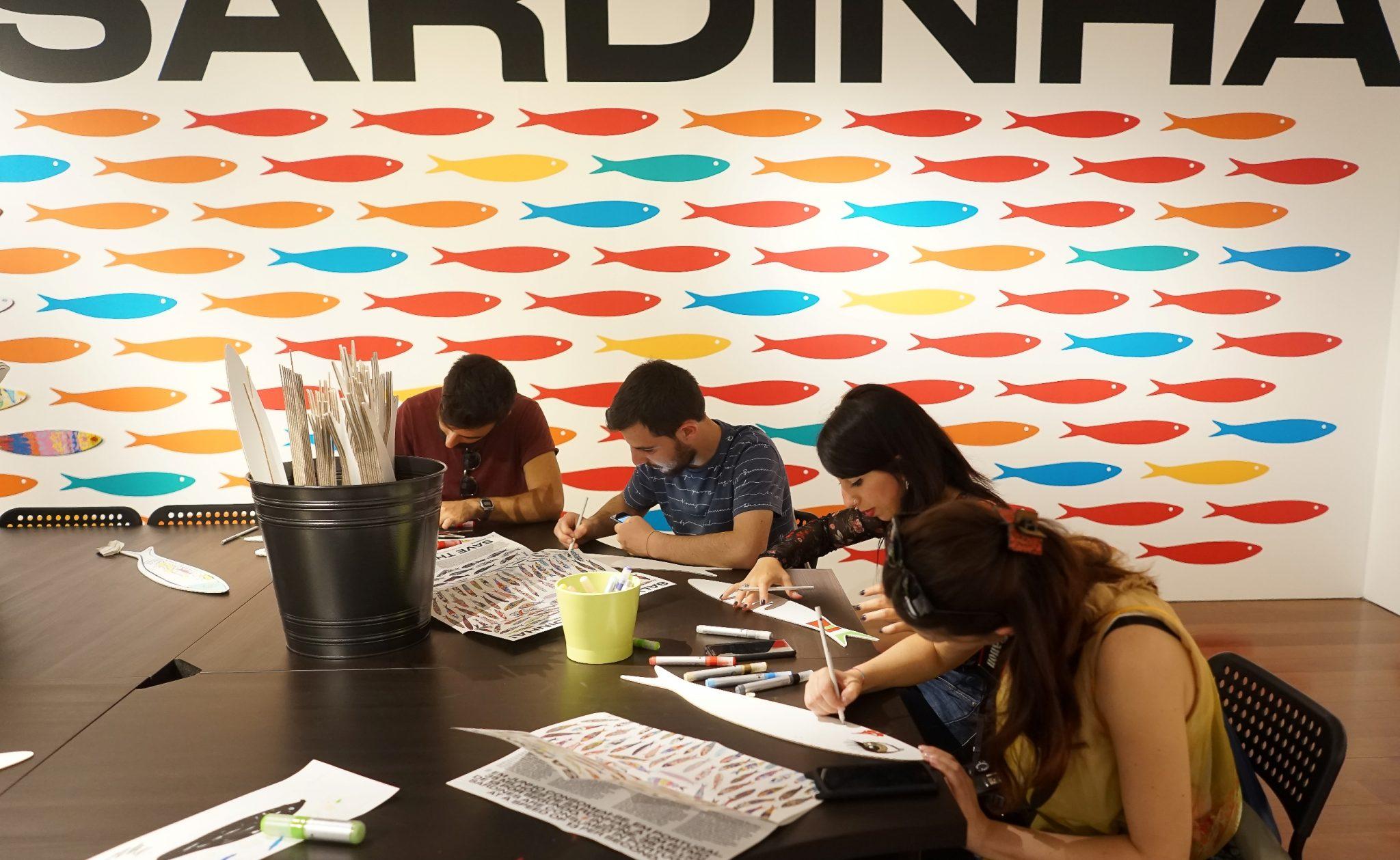 Quatro pessoas desenham em cartões com a silhueta de uma sardinha em cima de uma mesa preta. Atrás deles uma parede com silhuetas de sardinhas coloridas