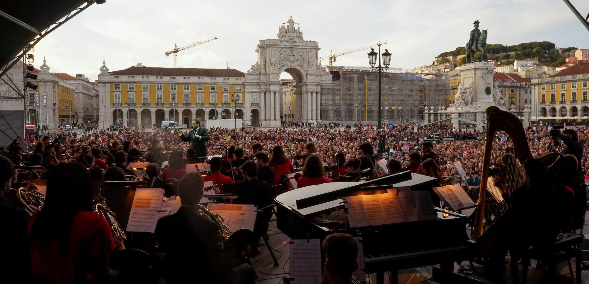 Vista do palco para a plateia. Em primeir plano, um piano, uma harpa e vários músicos. Em segundo plano, a plateia e o cenário da Praça do Comércio com a estátua D. José e o Arco da Rua Augusta