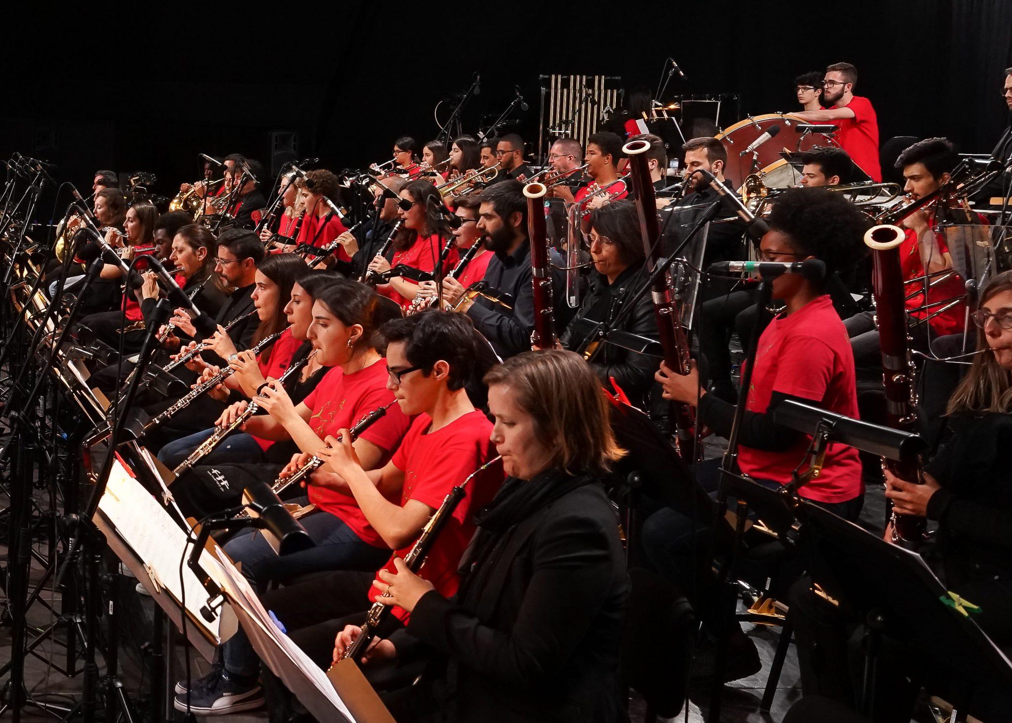 Elementos de uma orquestra (alguns de camisa preta outros de t-shirt vermelha) tocam vários instrumentos de sopro
