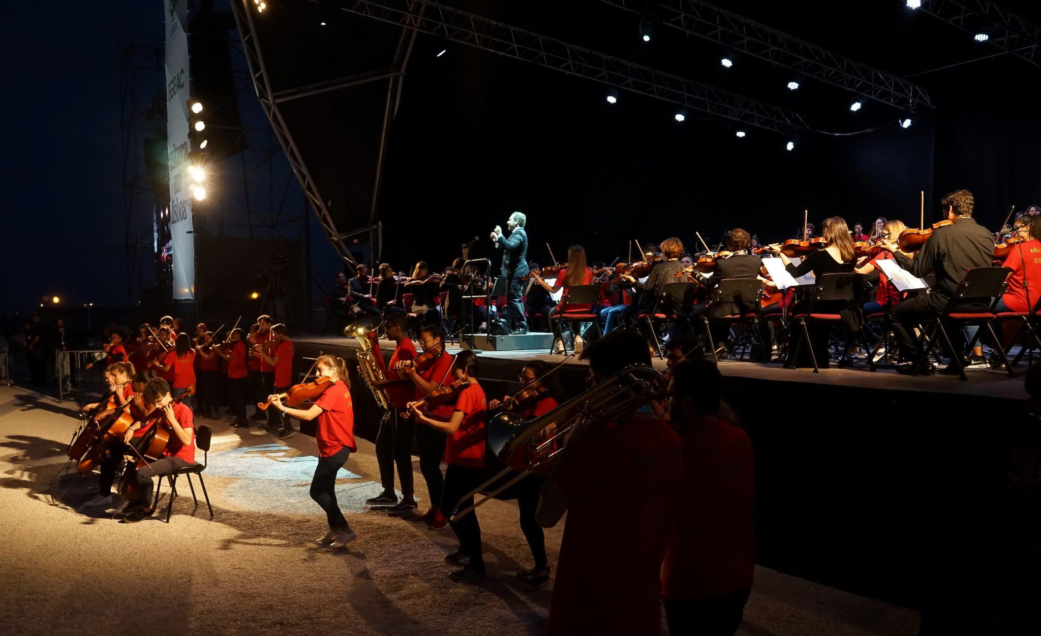 Um palco com uma orquestra e maestro de lado para o observador. Em baixo do palco, vários músicos com t-shirts tocam vários instrumentos