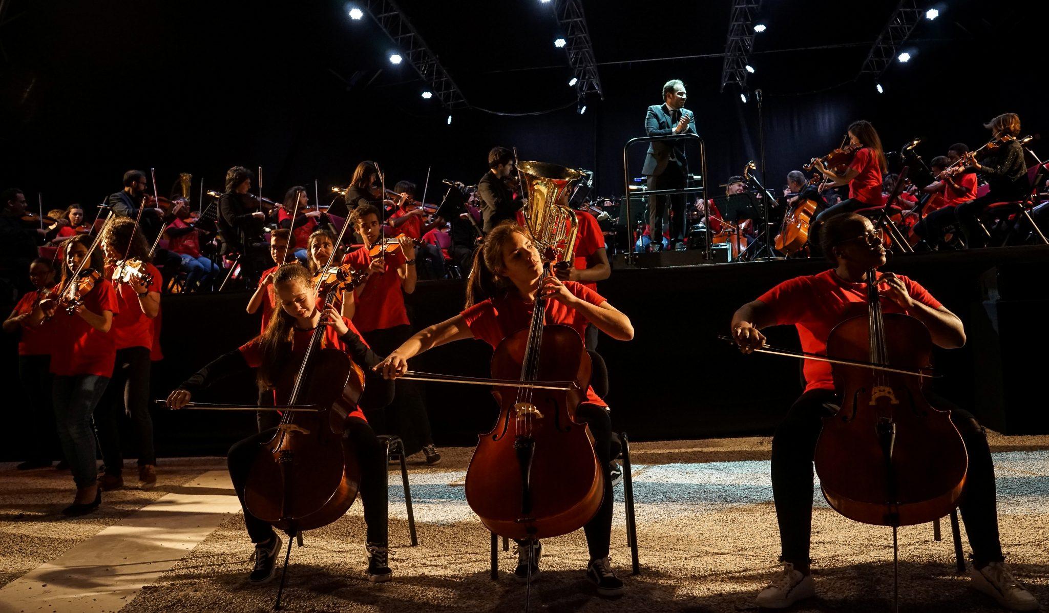 Em primeiro plano e de frente para o observador, três raparigas de t-shirt encarnada tocam violoncelo. Em segundo plano, jovens vestidos da mesma forma tocam violino e, mais atrás, um palco com uma orquestra