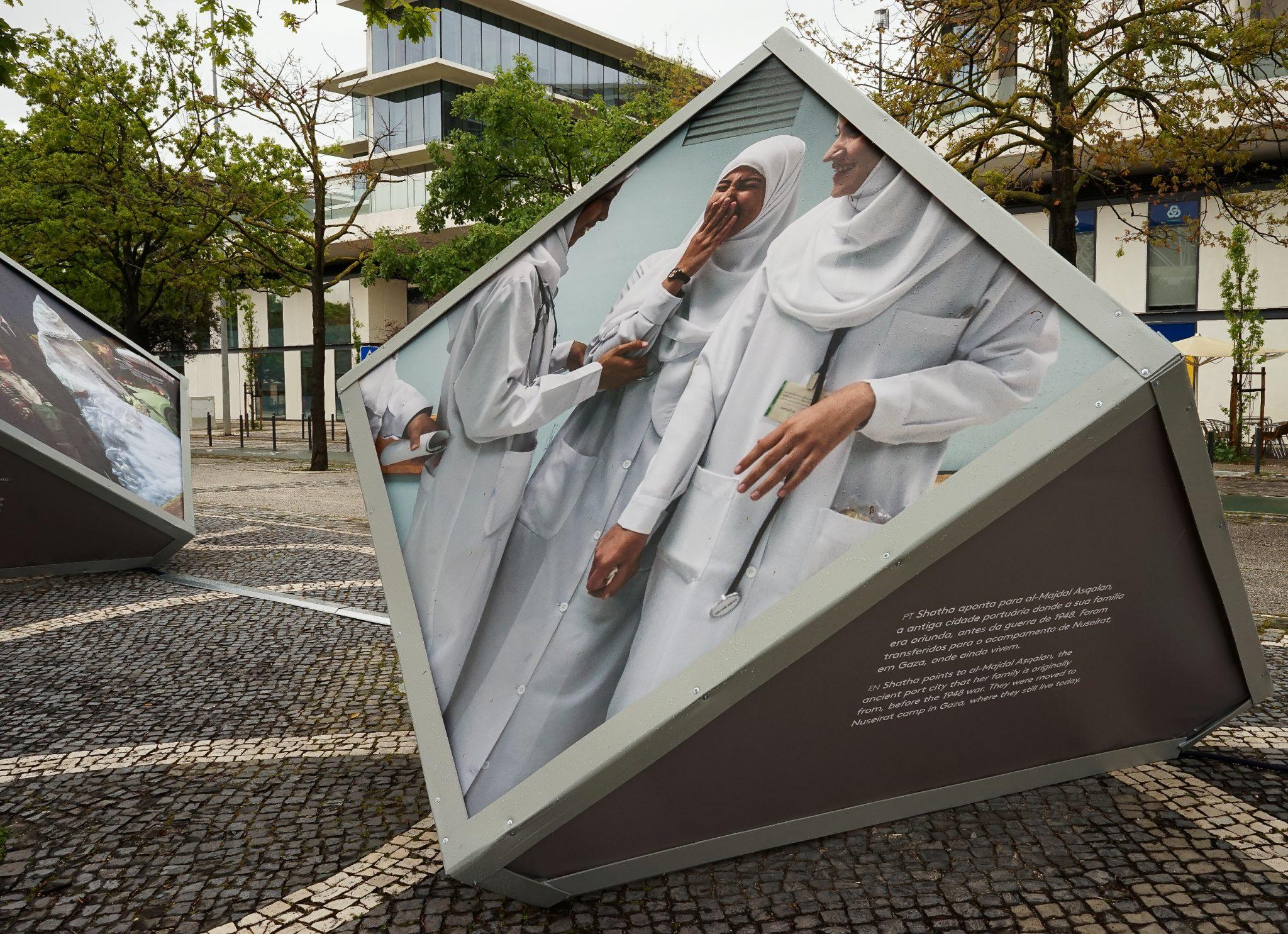 Cubo inclinado, e na diagonal para o observador, exibindo uma fotografia de jovens palestinianas com véus brancos, que integra a exposição