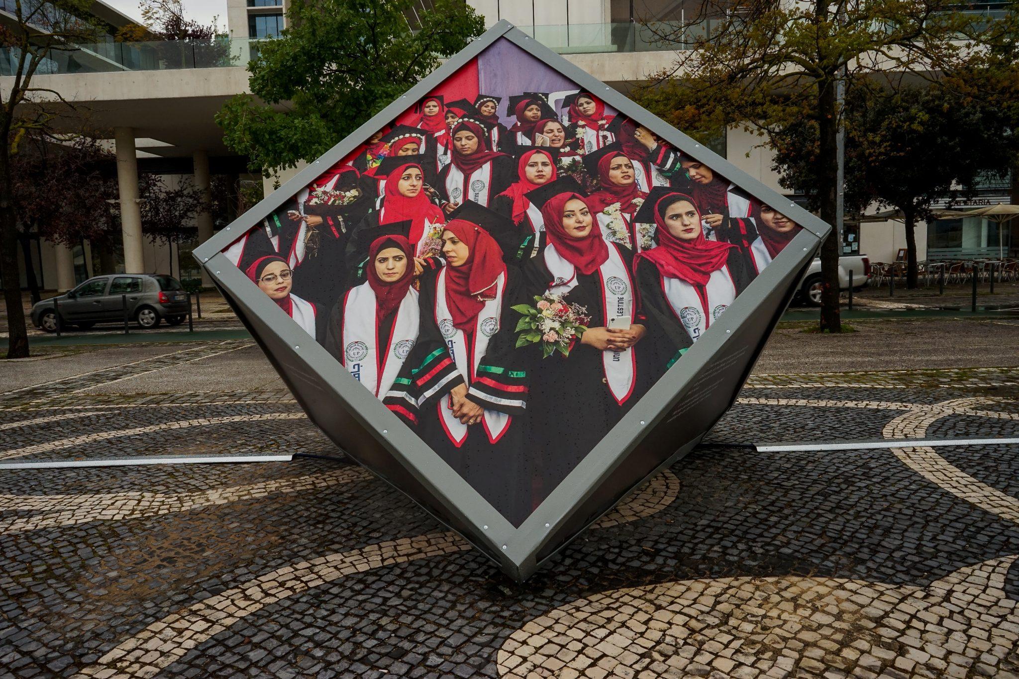 Cubo inclinado exibindo uma fotografia de um grupo de jovens palestinianas com véus vermelhos, de frente para o observador, que integra a exposição