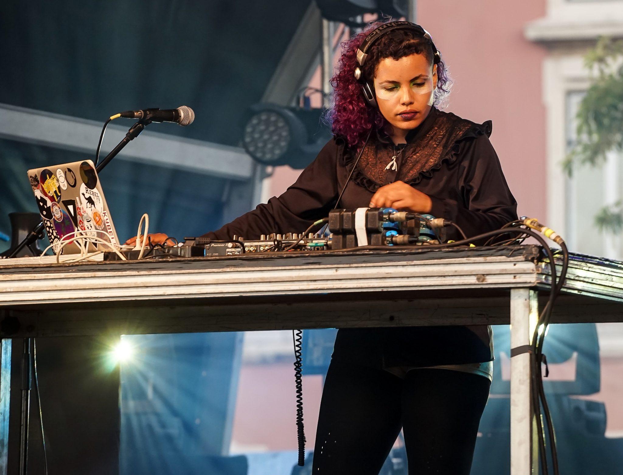 Mulher de cabelo roxo e auscultadores na cabeça em frente a uma mesa de mistura e microfone.