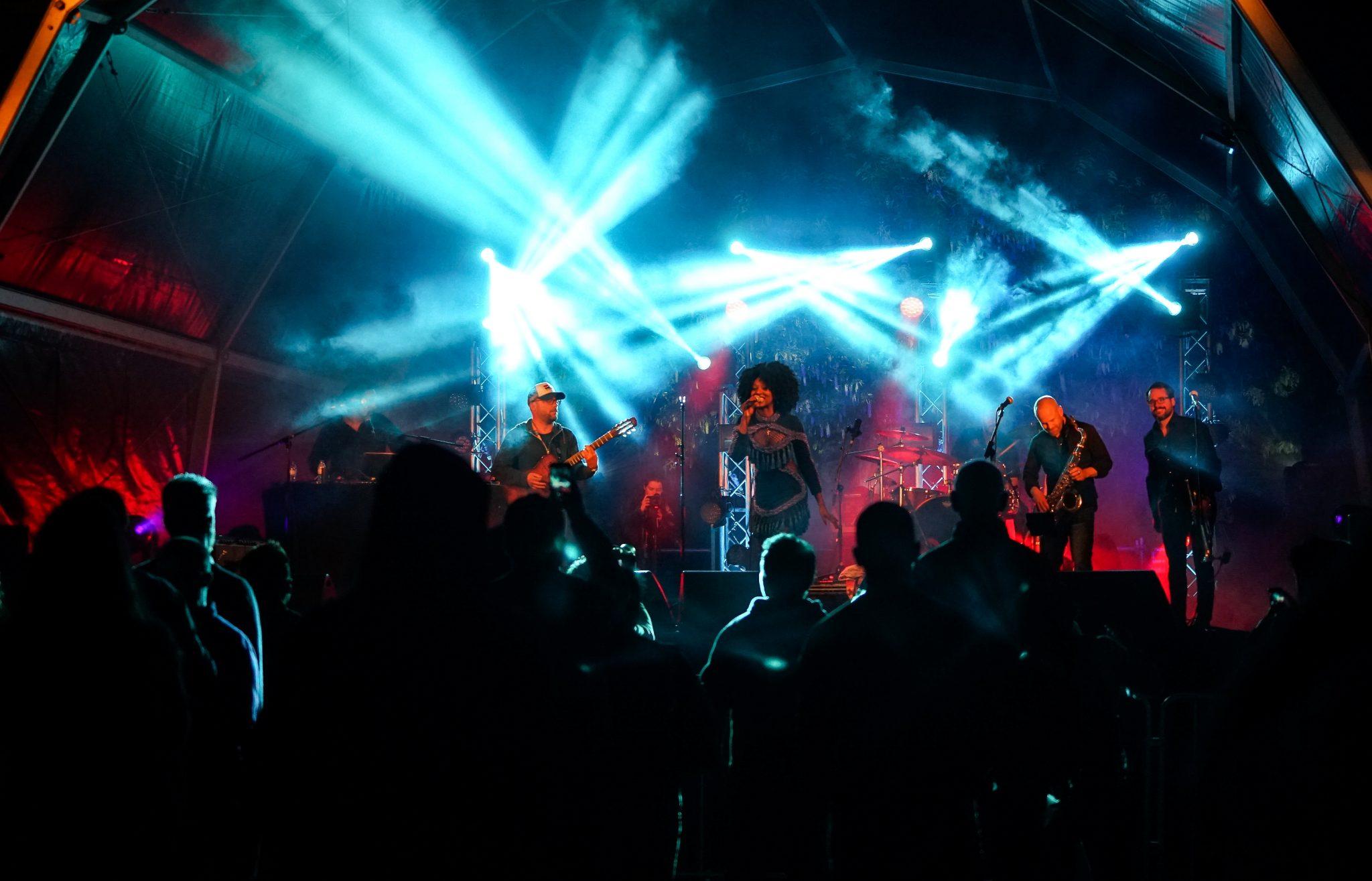 Banda composta por cinco elementos, com a vocalista ao centro, atua à noite, num palco iluminado por luzes azuis.