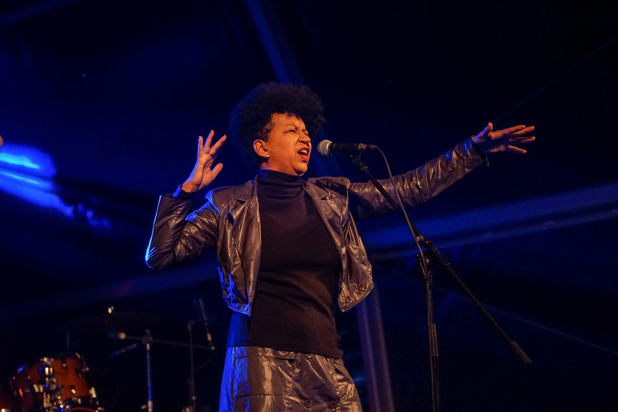 De lado para o observador, mulher vestida de preto atua frente a um microfone com um dos braços esticados para a sua frente.