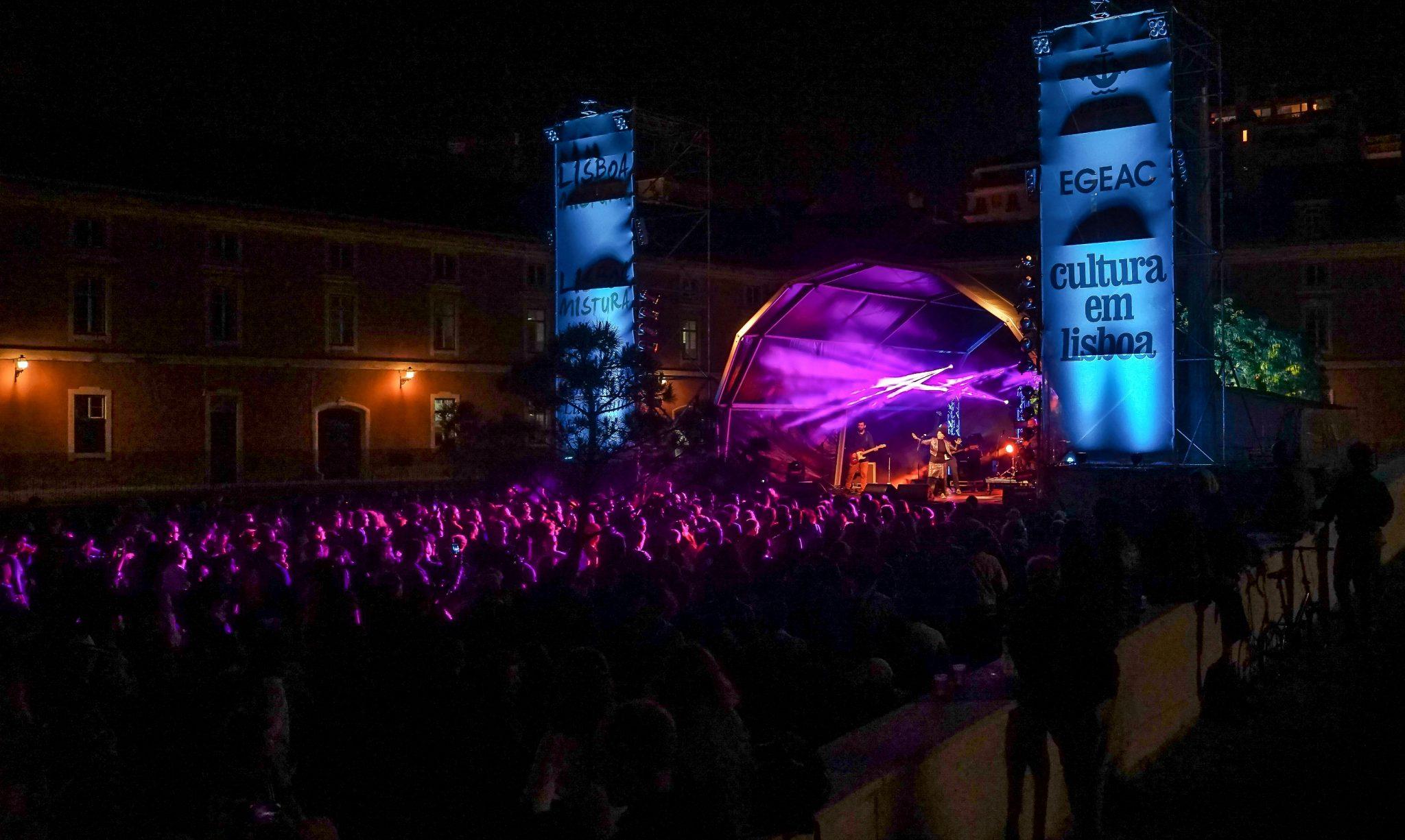 De lado para o observador, vista nocturna do palco com luzes roxas a incidirem sobre o público.