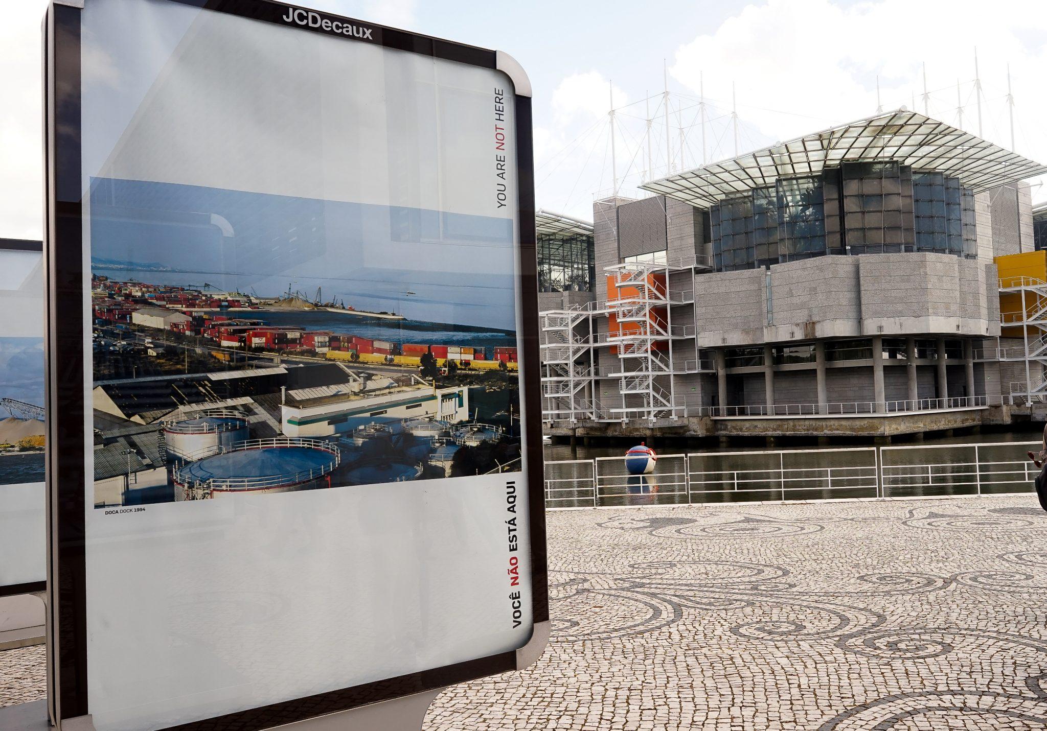 Em primeiro plano, um mupi com uma fotografia da antiga Doca dos Olivais antes da construção da Expo98. Em segundo plano o edifício do Oceanário.