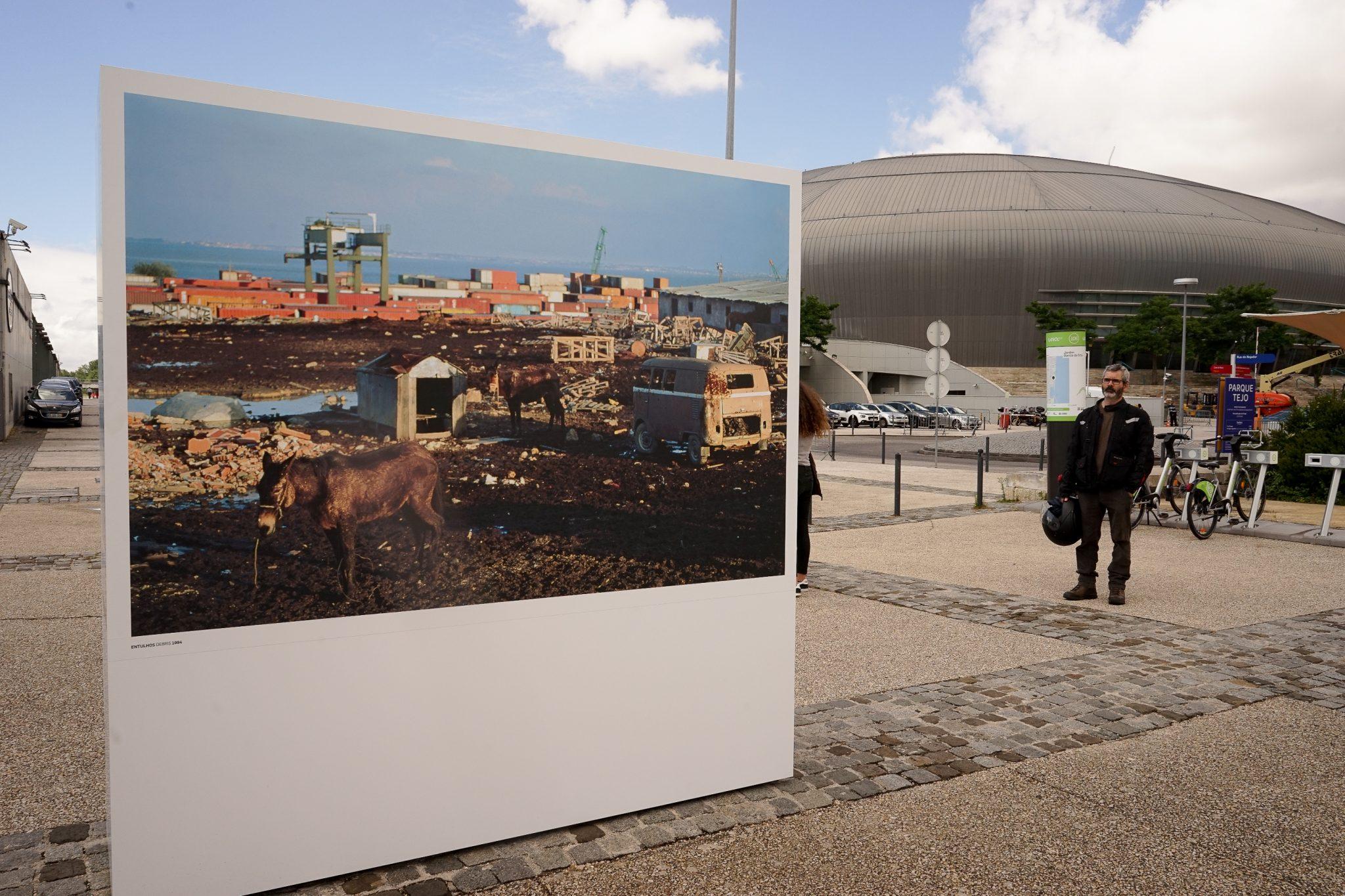 Em primeiro plano, uma estrutura com uma fotografia da zona onde foi construída a Expo98 onde figuram dois burros e uma área de contentores. Em segundo plano, a atual Altice Arena.