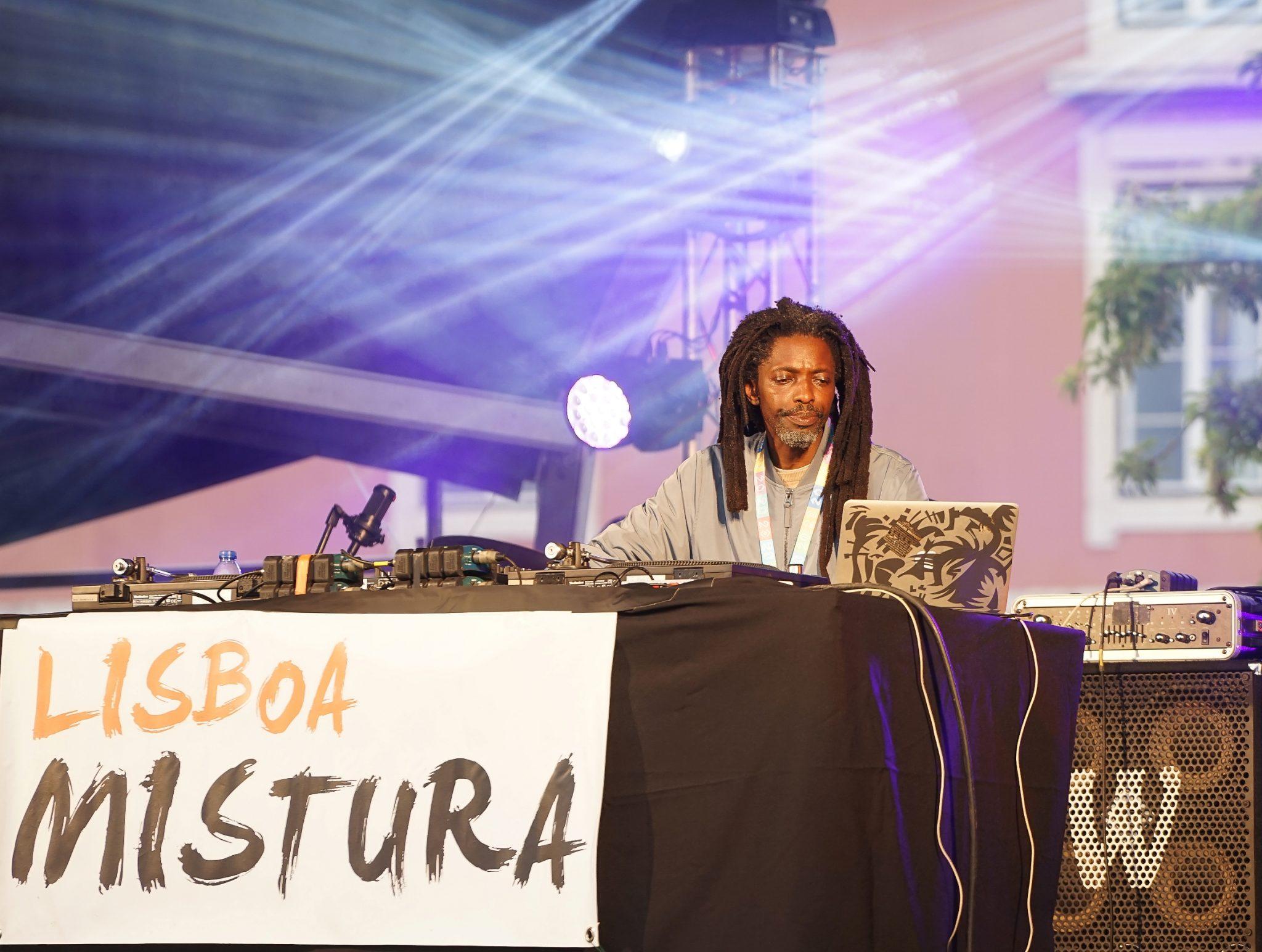 DJ Johnny em cima do palco com a mesa de mistura e computador