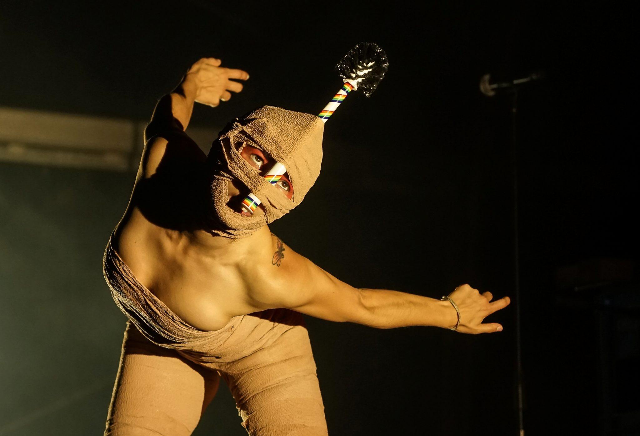 Uma bailarina, vestida com ligaduras, dança em palco no espetáculo dos IKOQWE