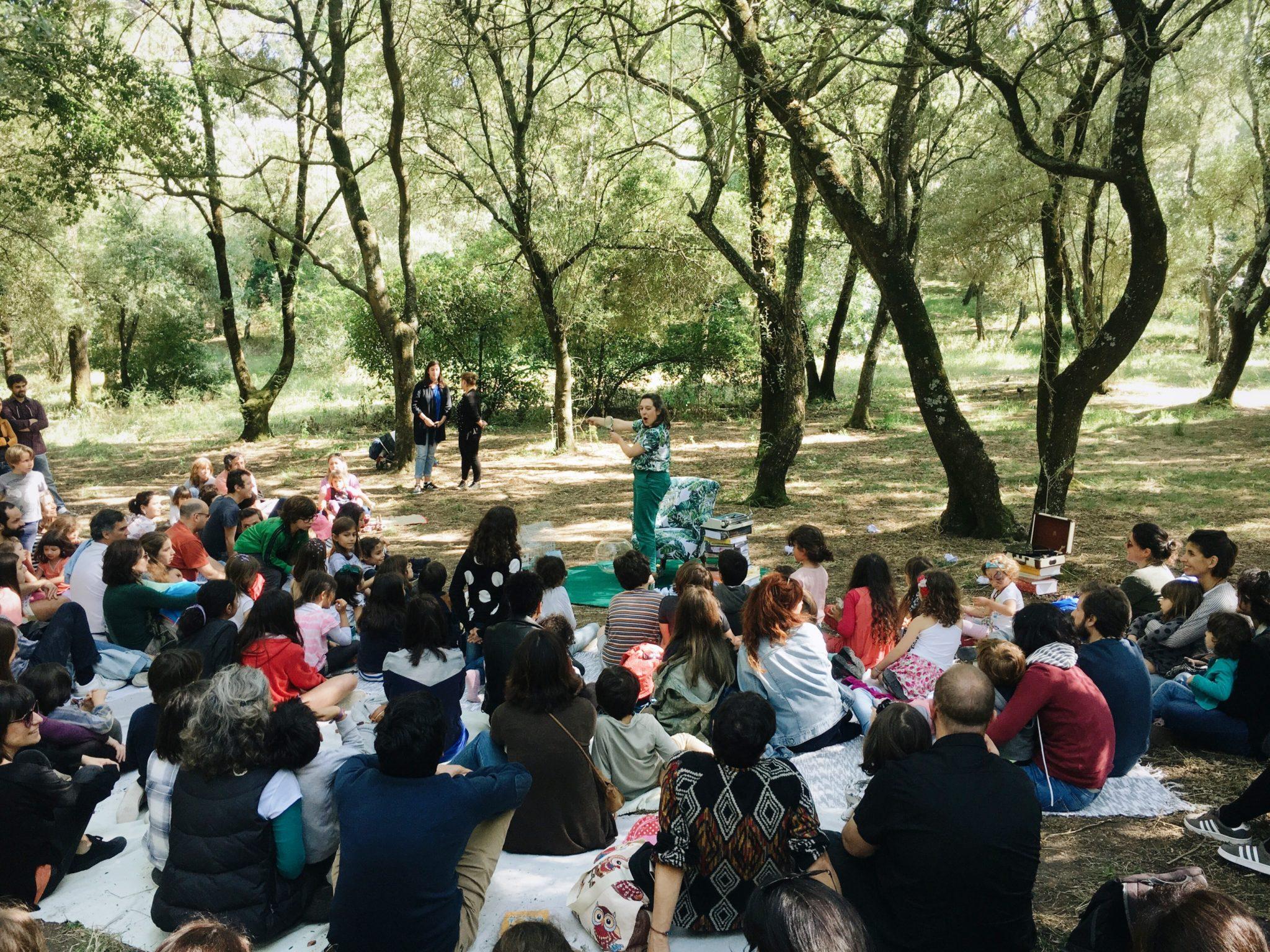 Plateia sentada no chão composta por adultos e crianças num jardim repleto de árvores. No centro uma actriz vestida de verde.