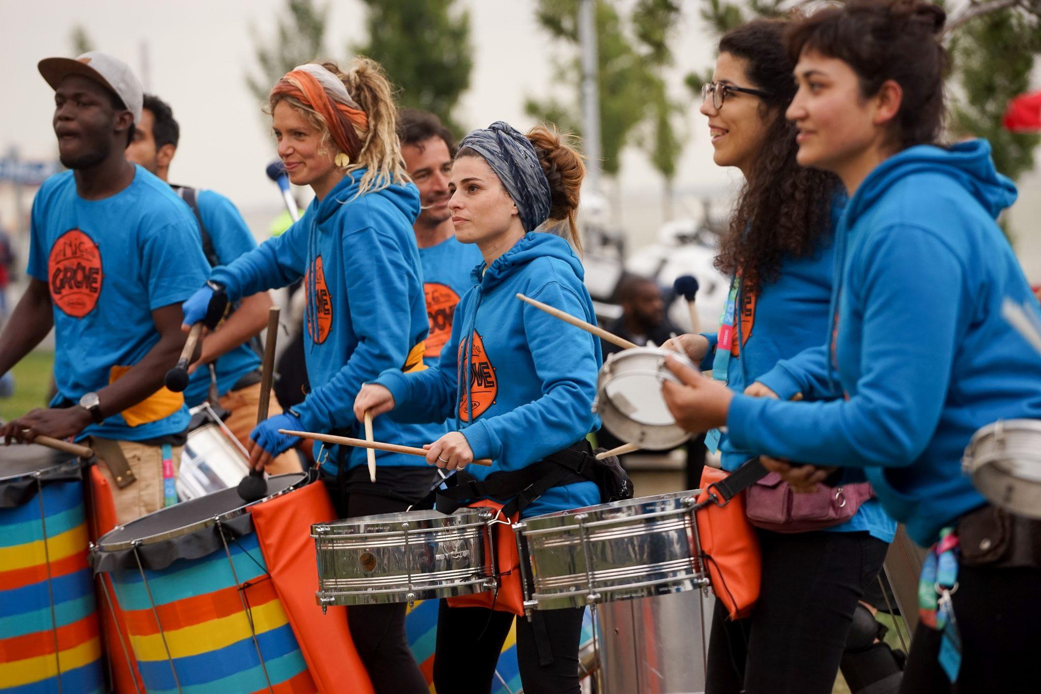 Grupo de mulheres e homens vestidos de camisolas azuis a tocar instrumentos de percussão de lado para o observador.