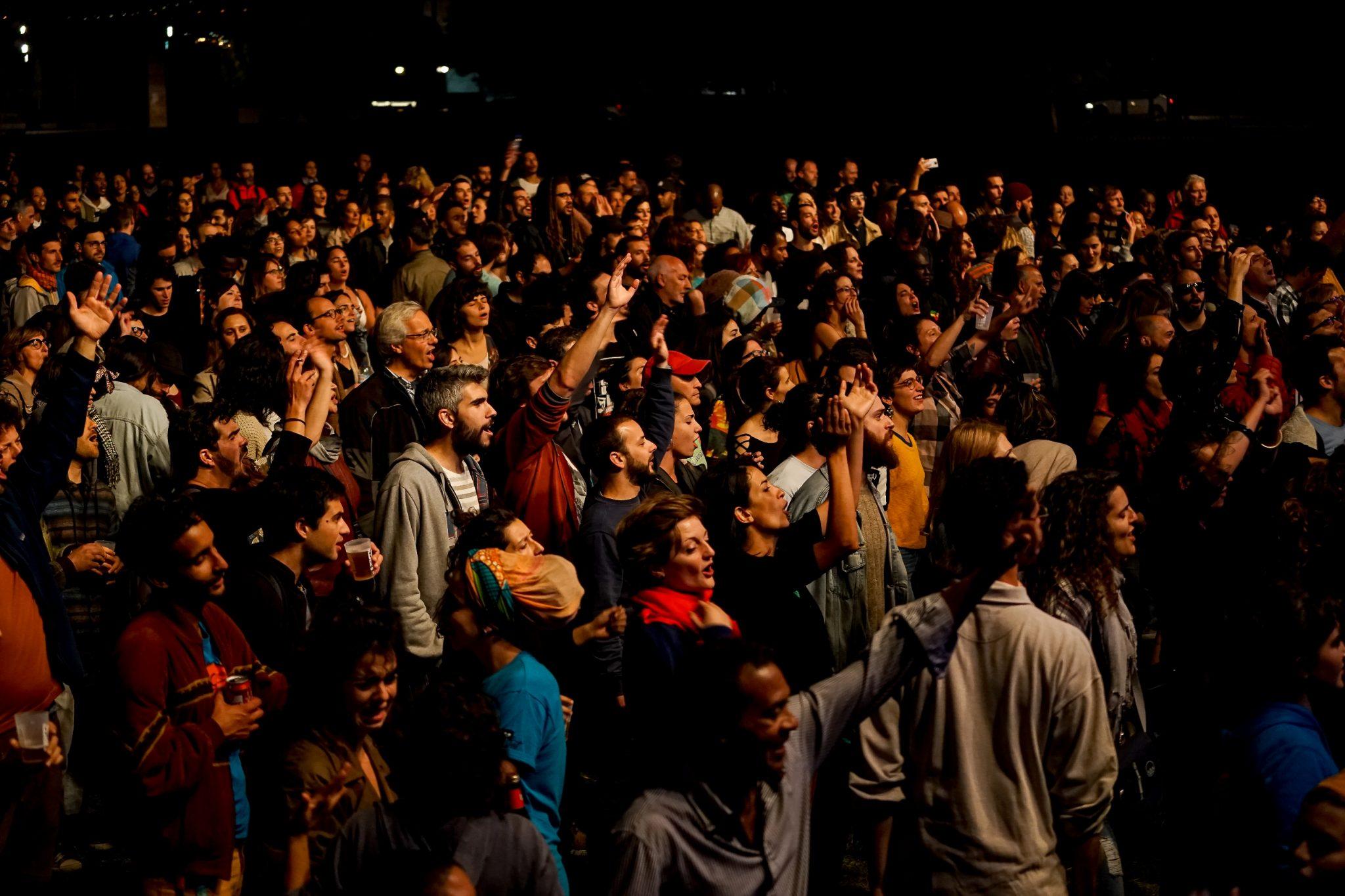 Visão geral do público a aplaudir de pé um espetáculo.
