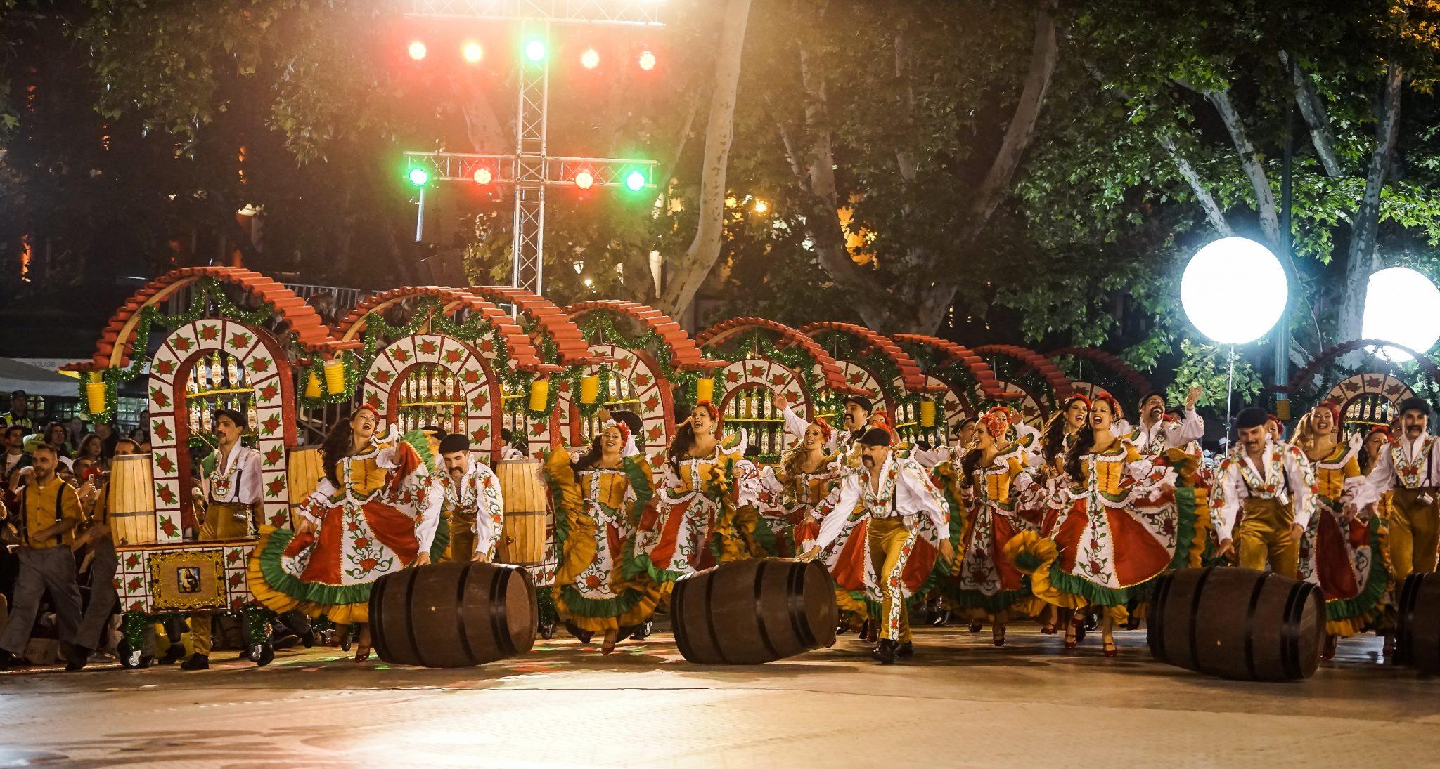 Homens e mulheres da Marcha de Alfama, vestidos em tons de vermelho, verde e dourado, desfilam na Avenida da Liberdade. Carregam os arcos, que representam tascas típicas, e ainda umas pipas de vinho.