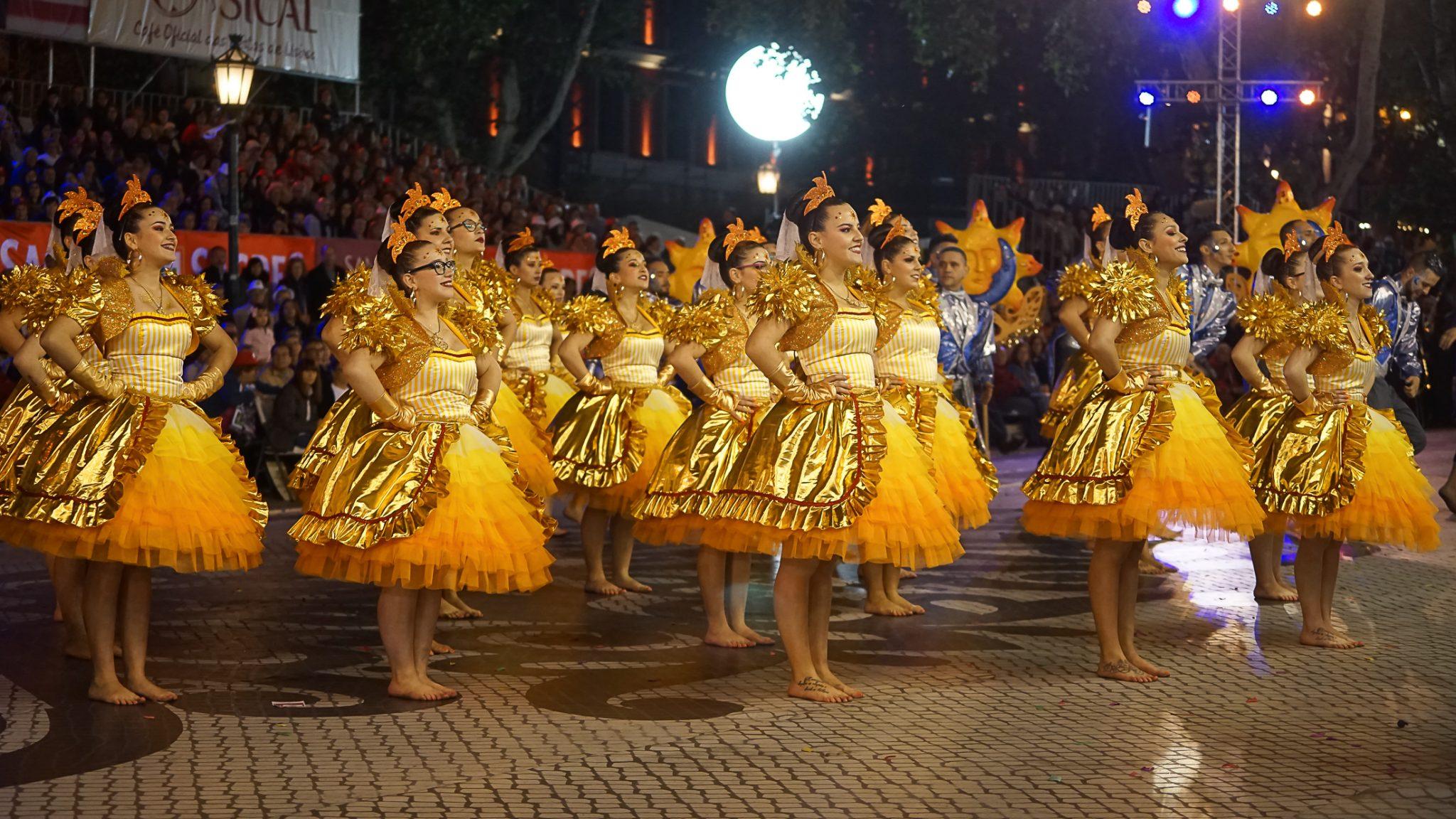 De lado para o observador, um grupo de mulheres vestida de saia e corpete amarelo e dourado sorri de mãos na cintura. O ambiente é nocturno e iluminado com holofotes