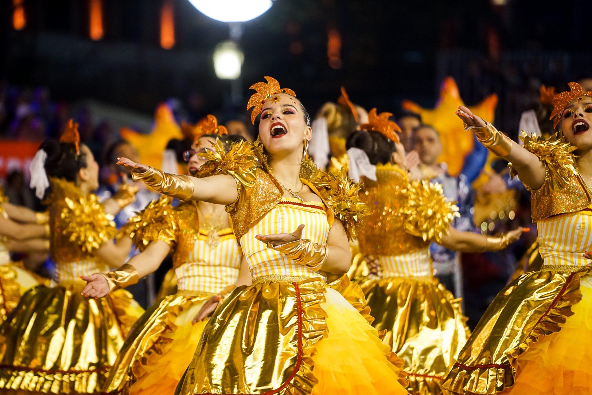 De frente para o observador, uma mulher com corpete e saia amarelos e dourados canta. Tem os braços virados para o lado esquerdo do observador